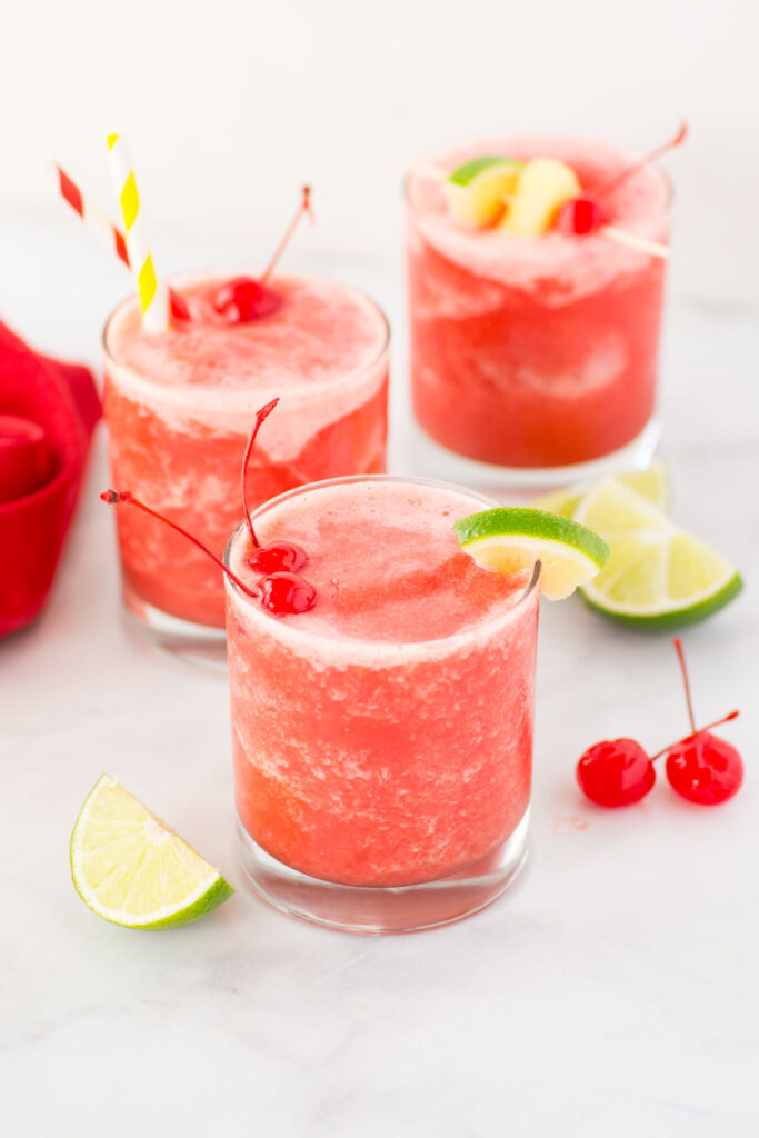 3 clear glasses filled with fruit slush and topped with lime segments and cherries.