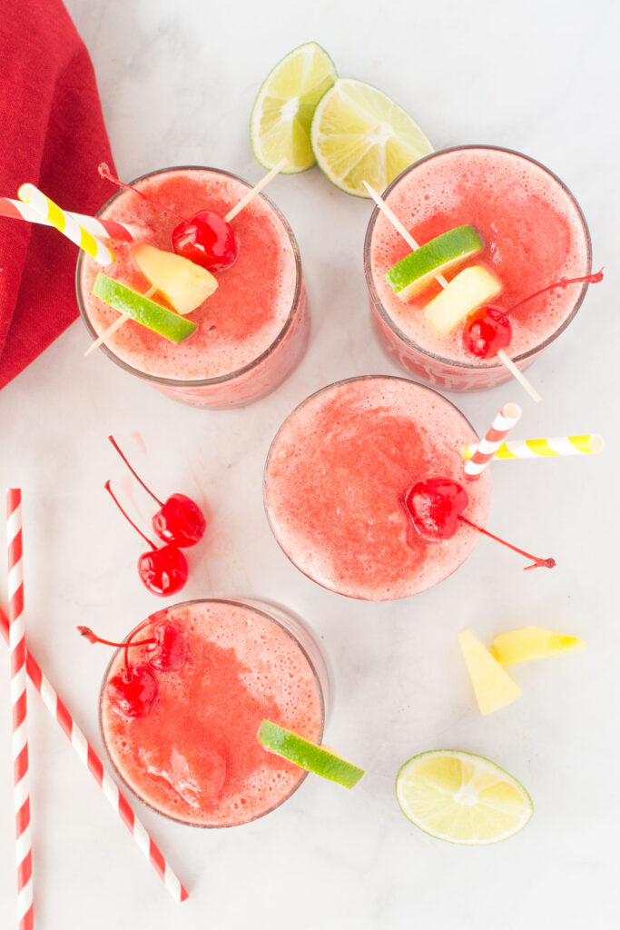 4 clear glasses filled with fruit slush and topped with lime segments, pineapple chunks and cherries.  There are some straws nearby and in one drink.