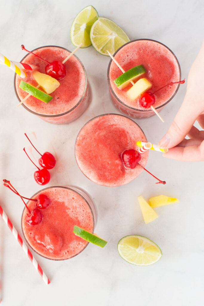 4 clear glasses filled with fruit slush and topped with lime segments, pineapple chunks and cherries. There is a hand putting a straw in one drink.