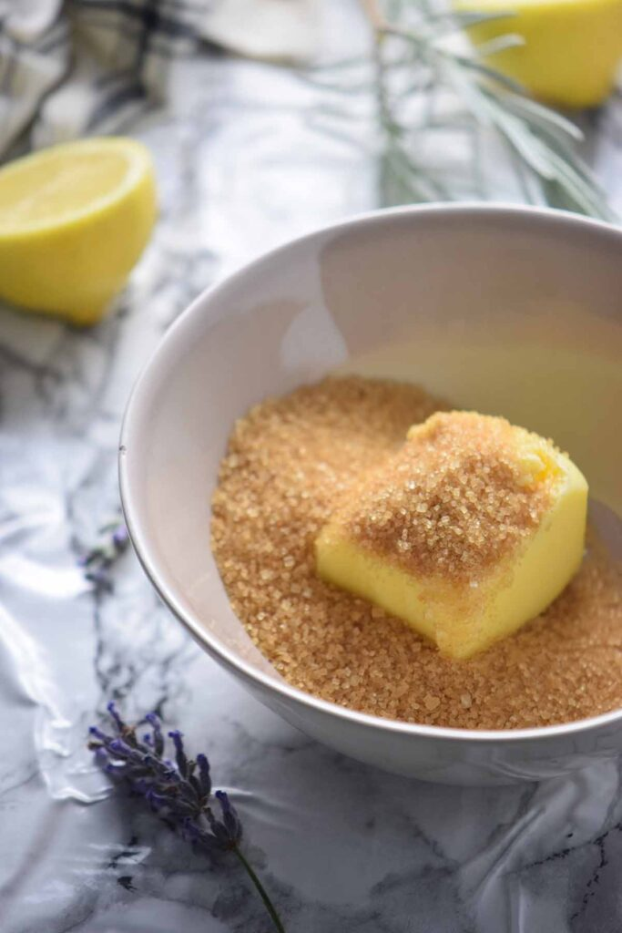 A white bowl with turbinado sugar and pat of yellow butter on a marble counter with lavender and a half lemon on the side.