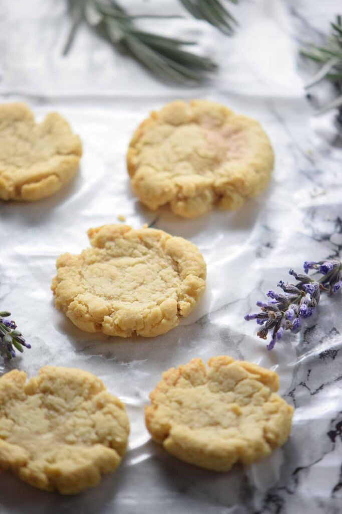 5 cookies laying out on a white and black marble counter with sprigs of lavender next to it.