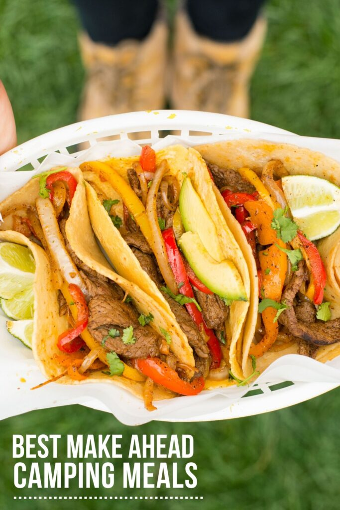 A white plastic basket full of tortillas filled with steak fajitas and limes on the side is being held up with two boots out of focus below. The words Best Make Ahead Camping Meals are in white and underlined in left lower corner.