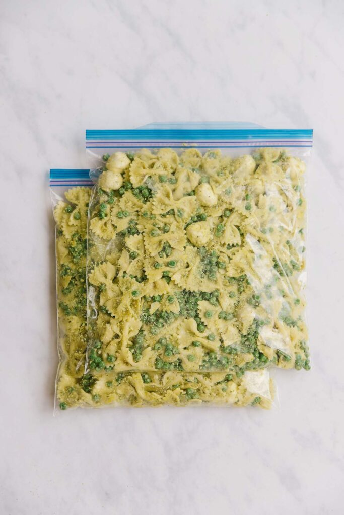 2 gallon-size zippered bags filled with pesto pasta salad.