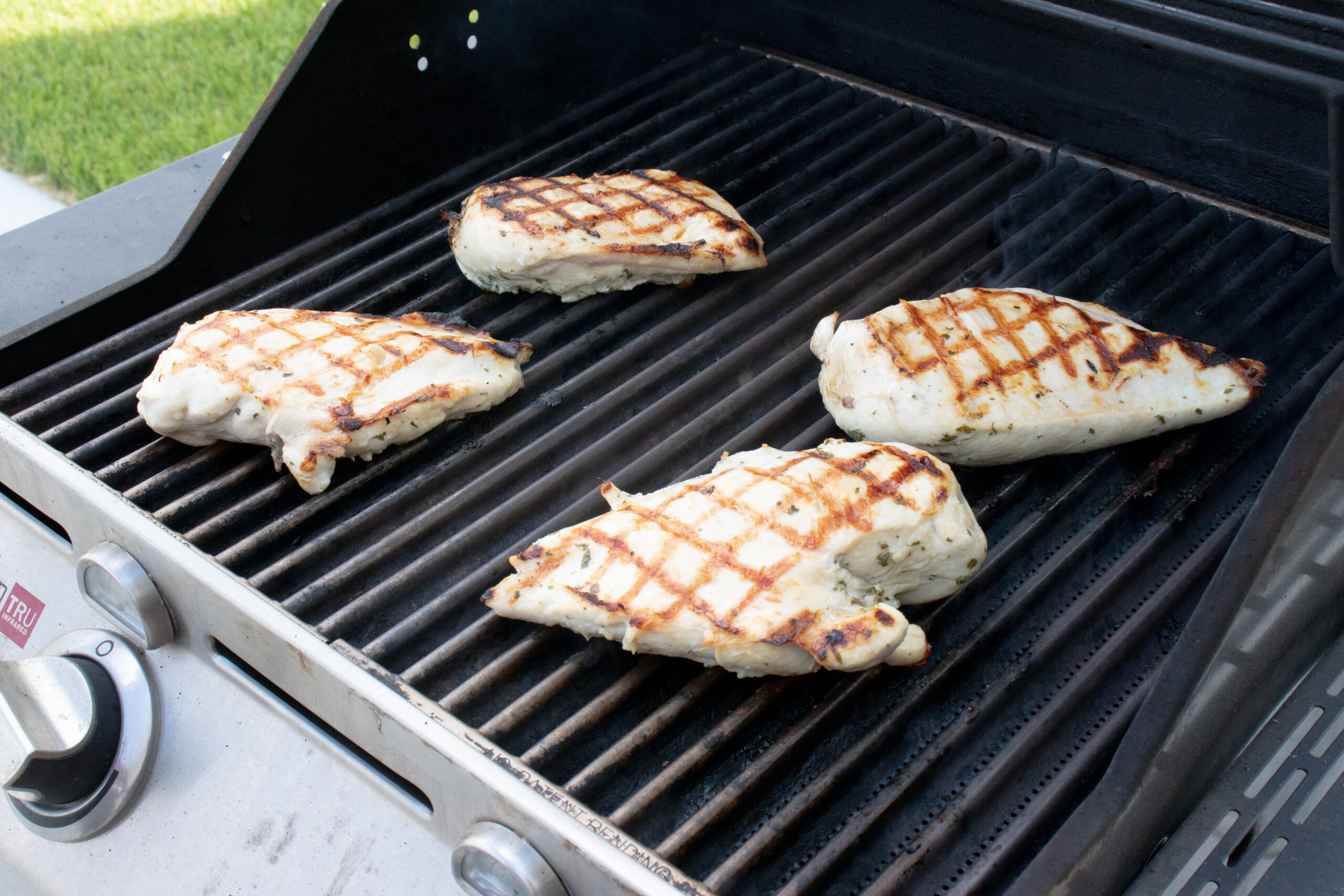 A grill with 4 grilled pieces of chicken.