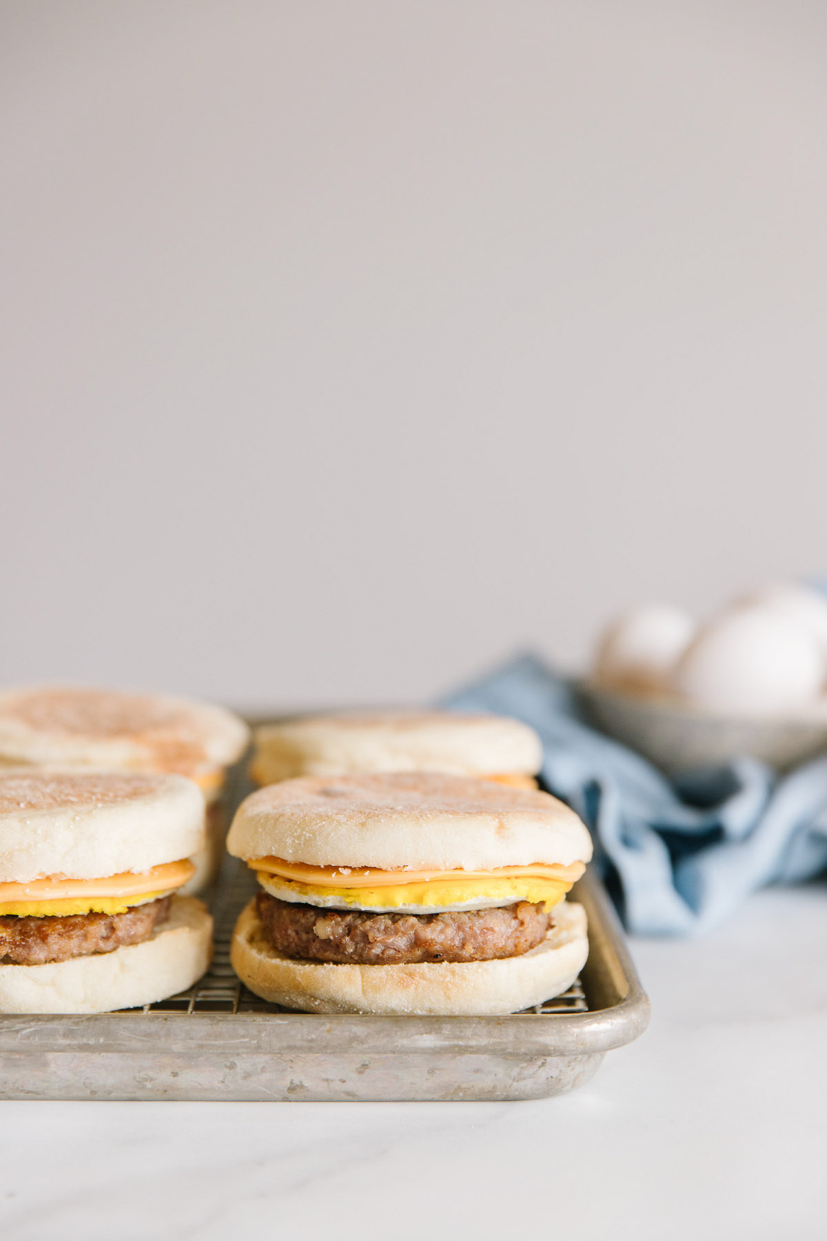 A pan with a wire tray with freezer breakfast sandwiches on it with a bowl of eggs on the side.