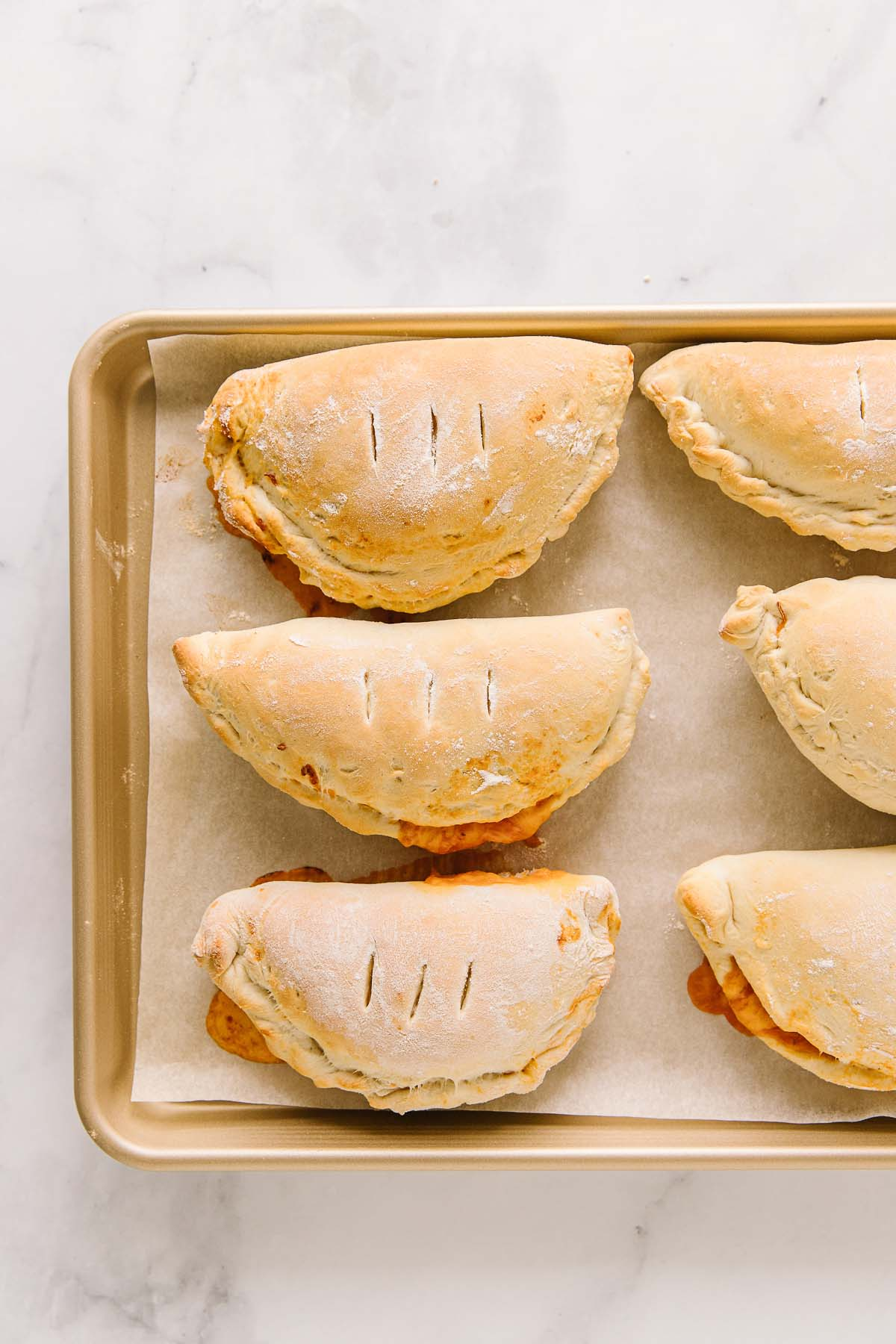 A parchment-lined cookie sheet with 6 cooked homemade hot pockets.