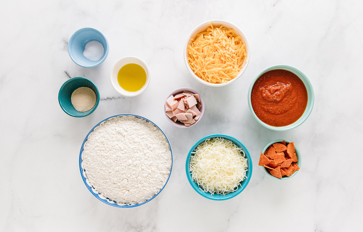 9 small bowls of differing sizes with Flour, Salt, Yeast, Olive oil, Water, Chopped ham or pepperoni, Shredded mozzarella cheese, Shredded cheddar cheese and Pizza sauce