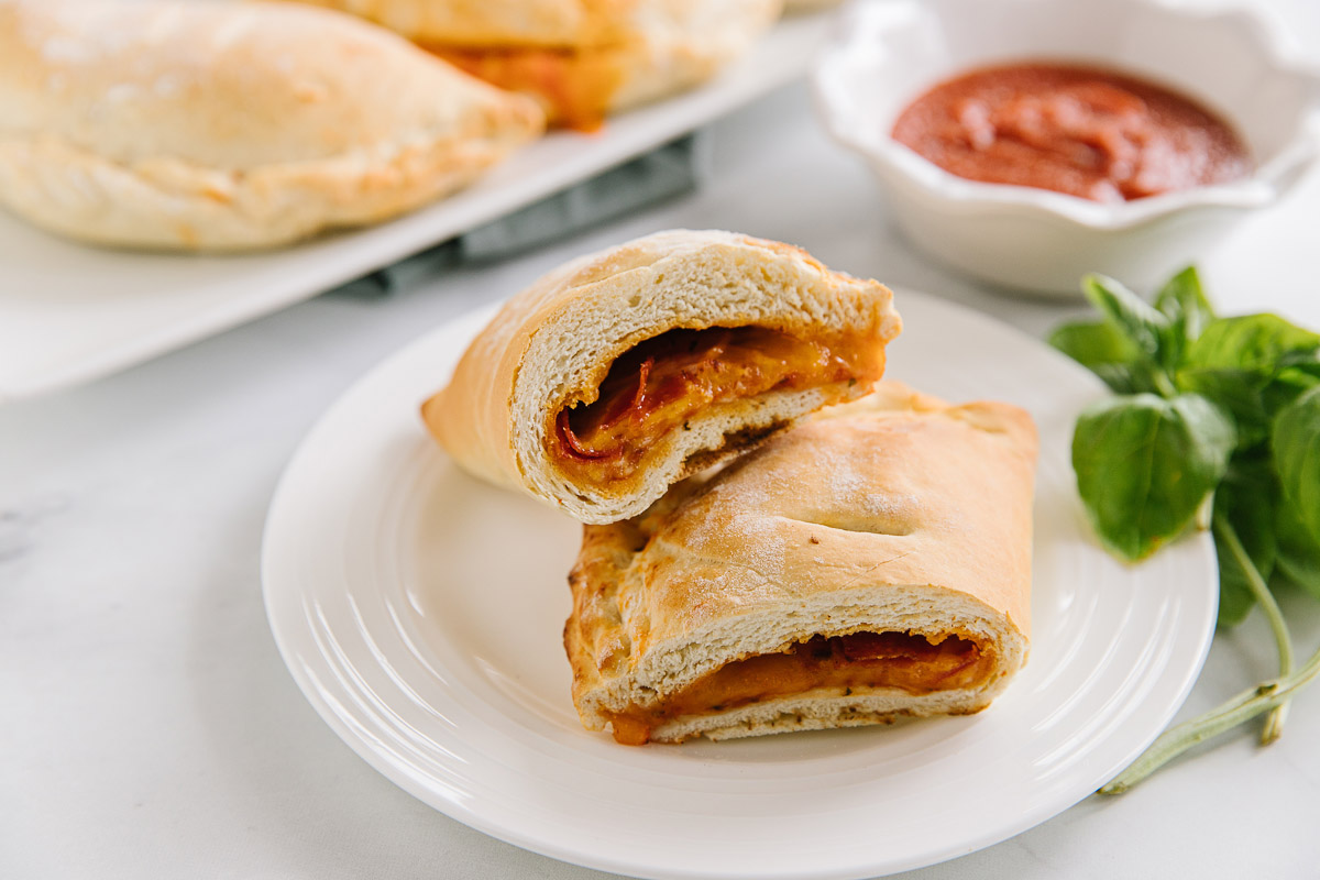 A white plate holds two halves of a cut homemade hot pocket with a cup of sauce on the side and whole hot pockets behind it.