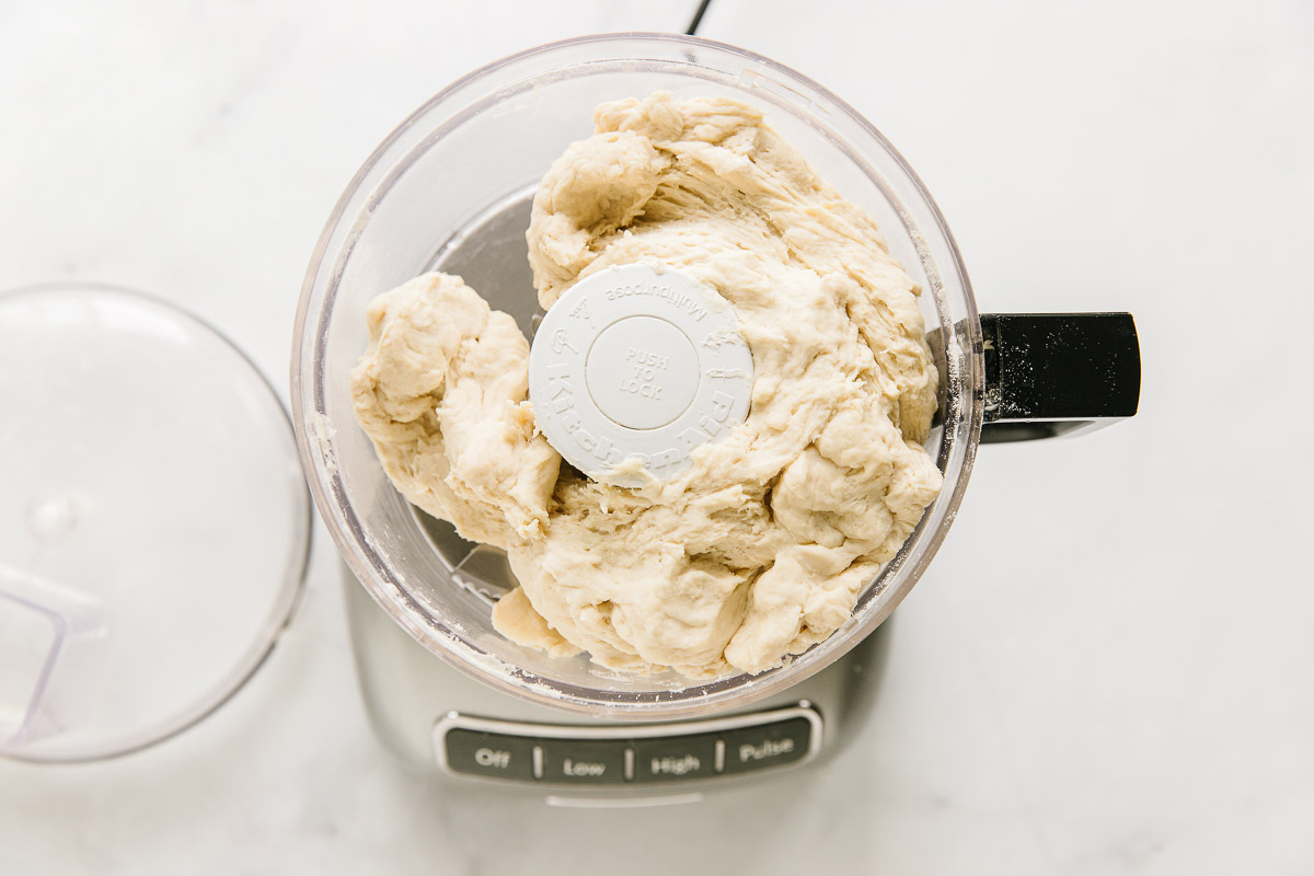 A food processor open with dough in it with the lid on the side.