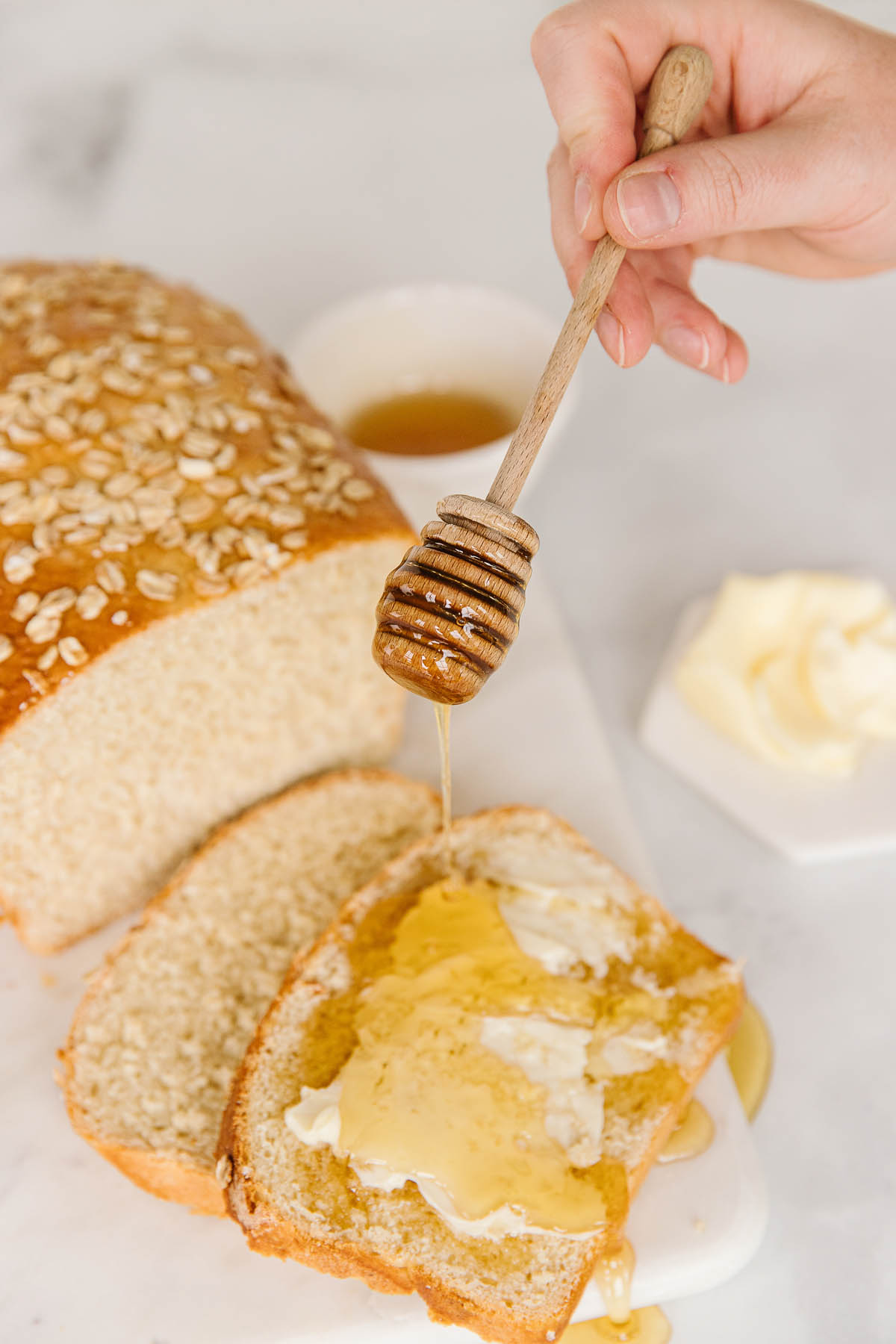 A loaf of honey oatmeal bread cut into slices with butter and honey on it with a hand drizzling honey on the sliced and buttered bread.