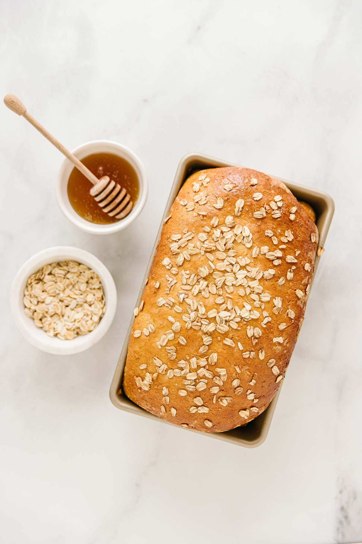Bread with oatmeal on top in a pan with two bowls on the side filled with honey and oatmeal.