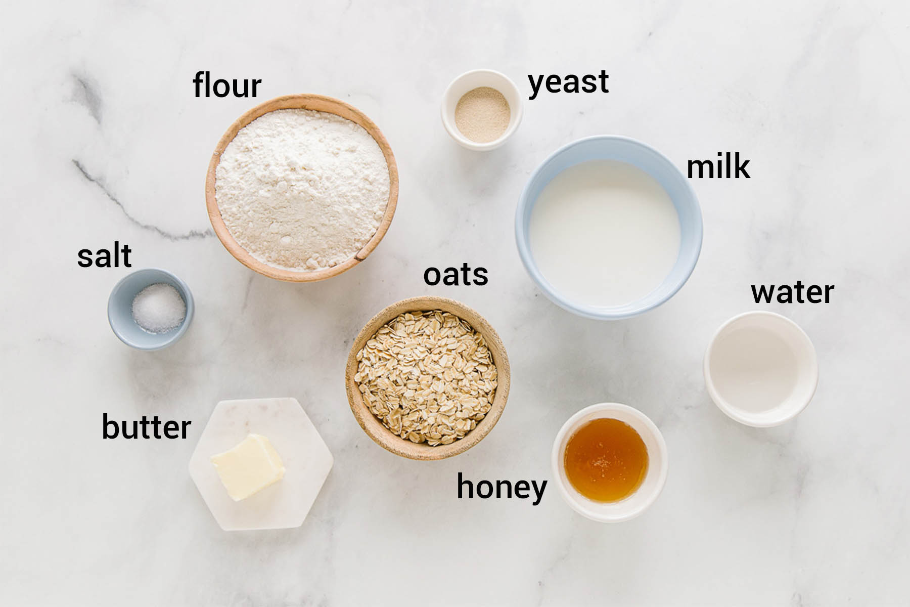Bowls of various sizes with these ingredients in them: flour, yeast, milk, water, honey, oats, butter, salt.