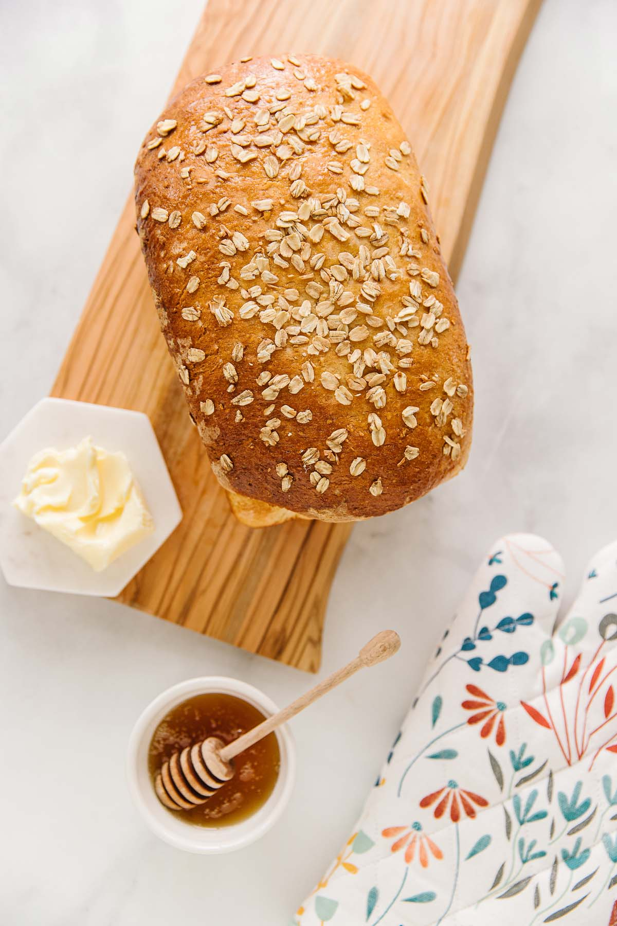 A honey oatmeal bread loaf on a wooden plank with a plate of butter and bowl of honey and a flowered oven mitt.