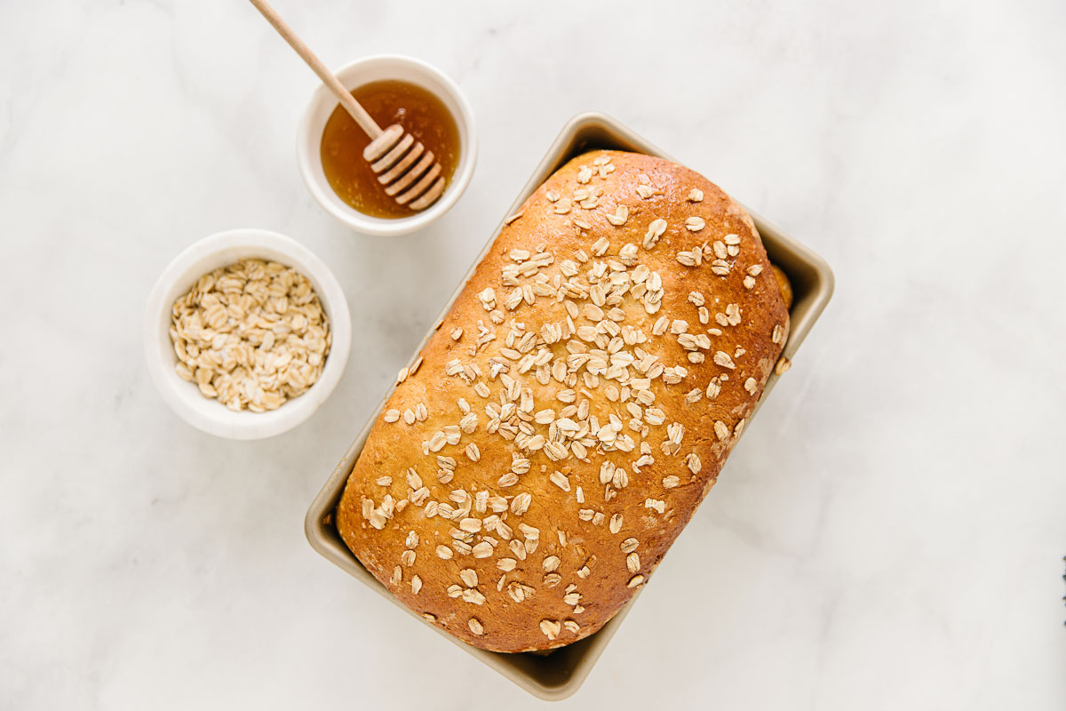 A load of honey oatmeal bread in a pan with two bowls of honey and oatmeal to the side of it.