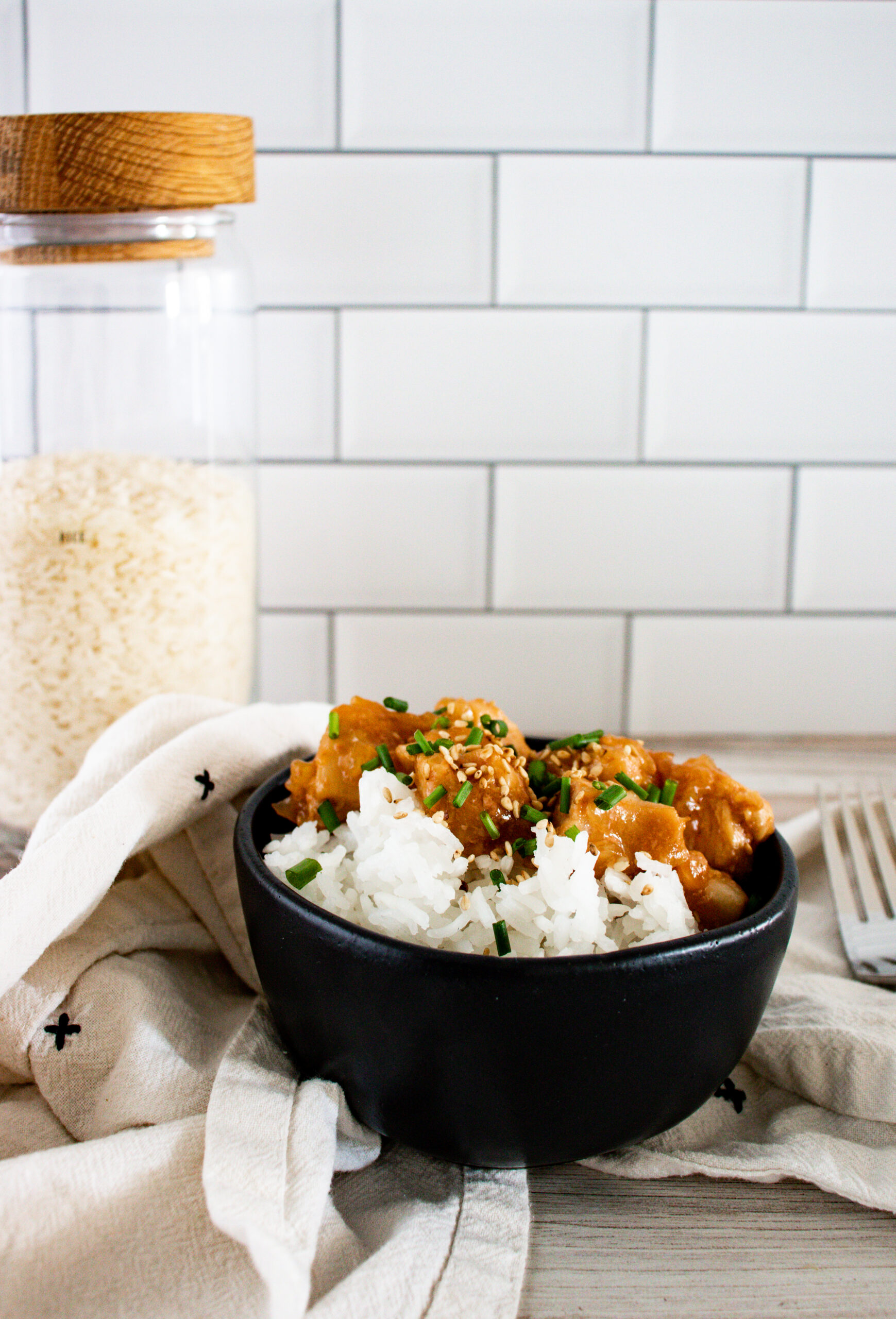 A black bowl of rice and teriyaki chicken with a white towel behind it with a fork and a container of rice behind it.