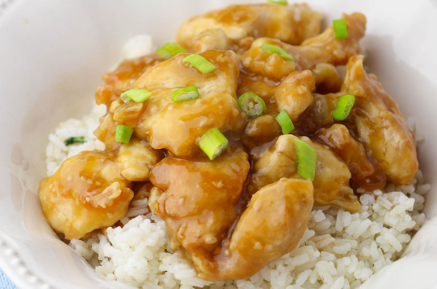 A white bowl of rice and orange chicken with green onions on it.