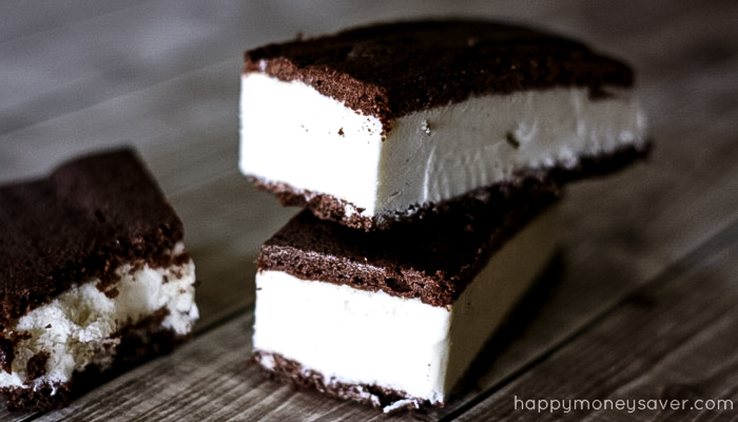A wood background with three ice cream sandwiches piled on it.