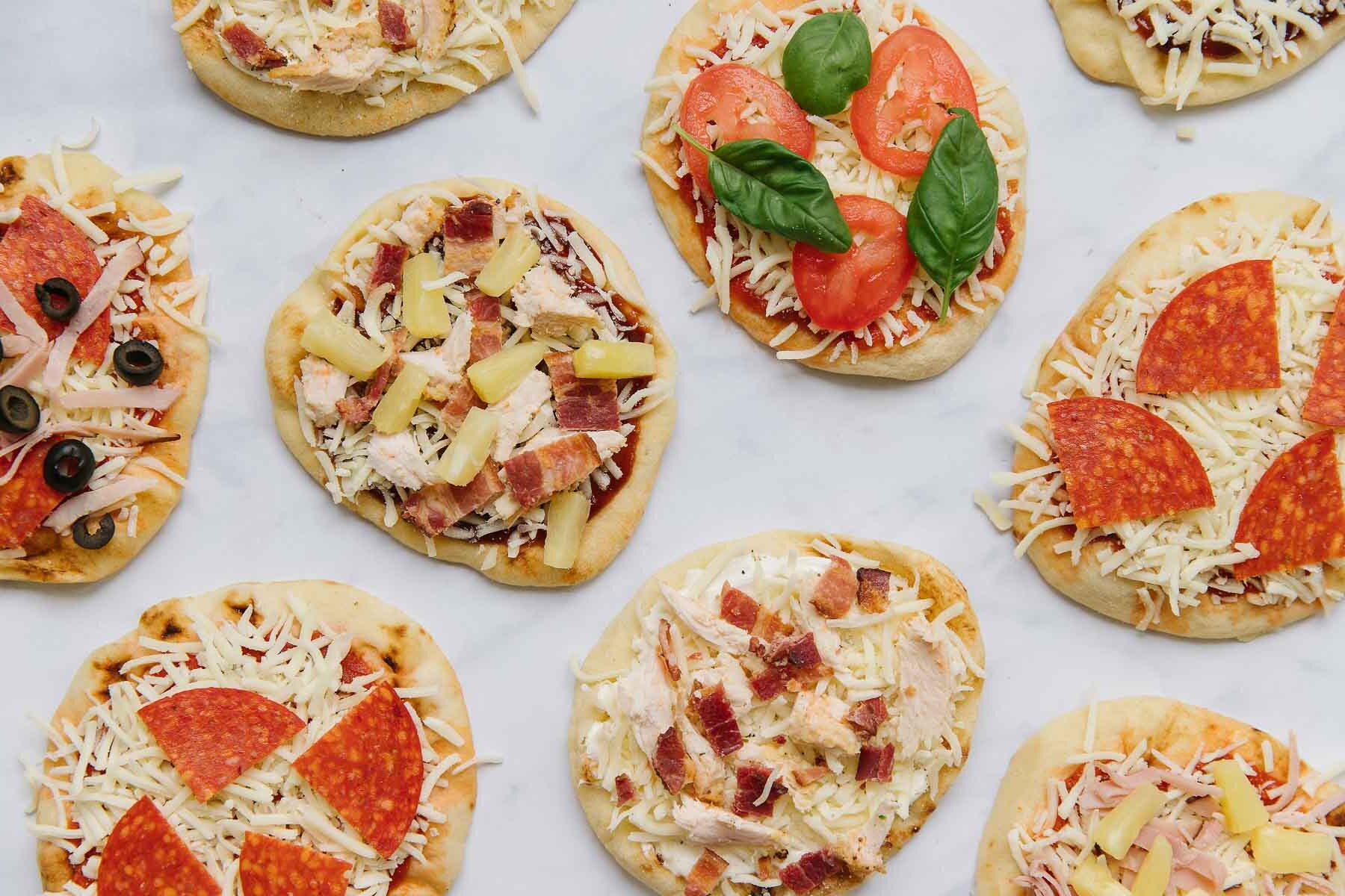 Different naan pizzas with different toppings on a white marble slab.