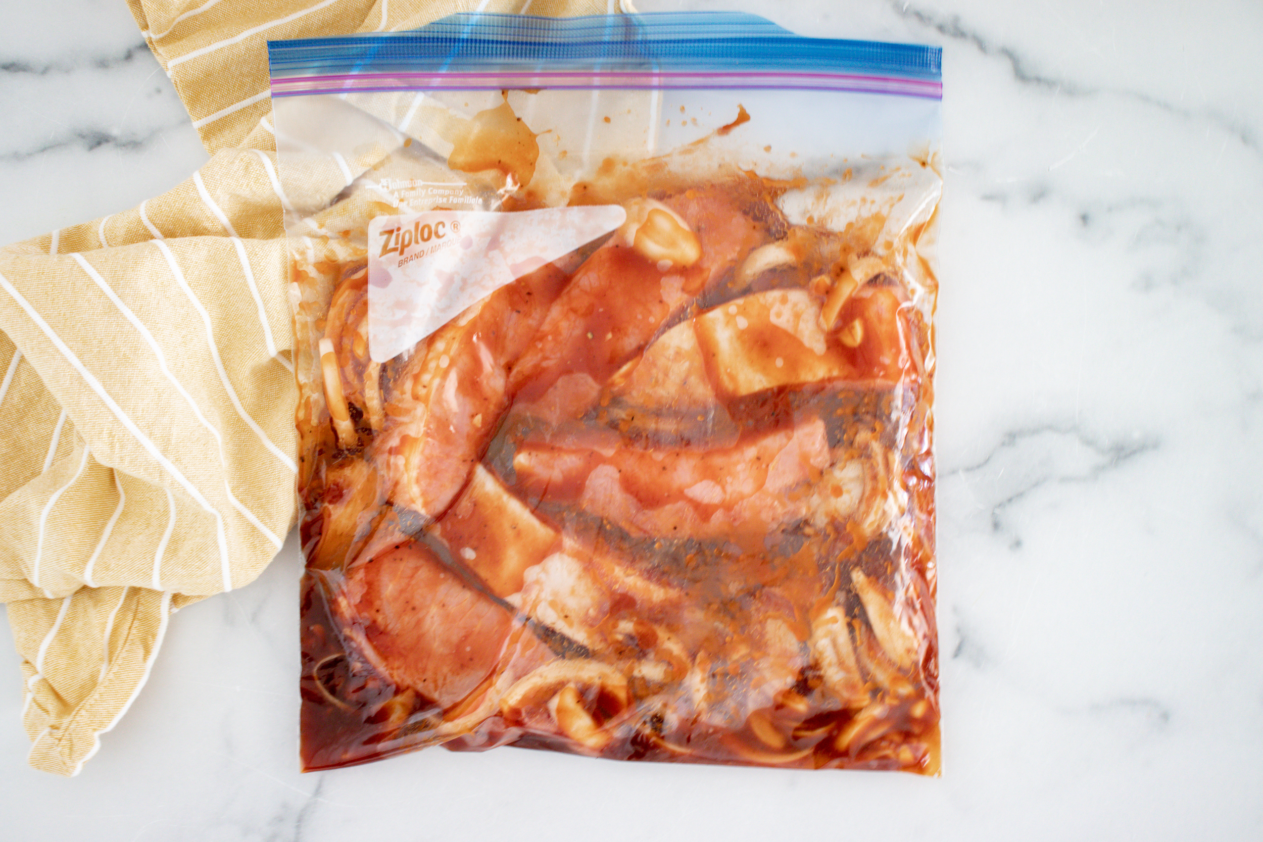 A gallon size resealable bag with uncooked ribs and sauce in it.