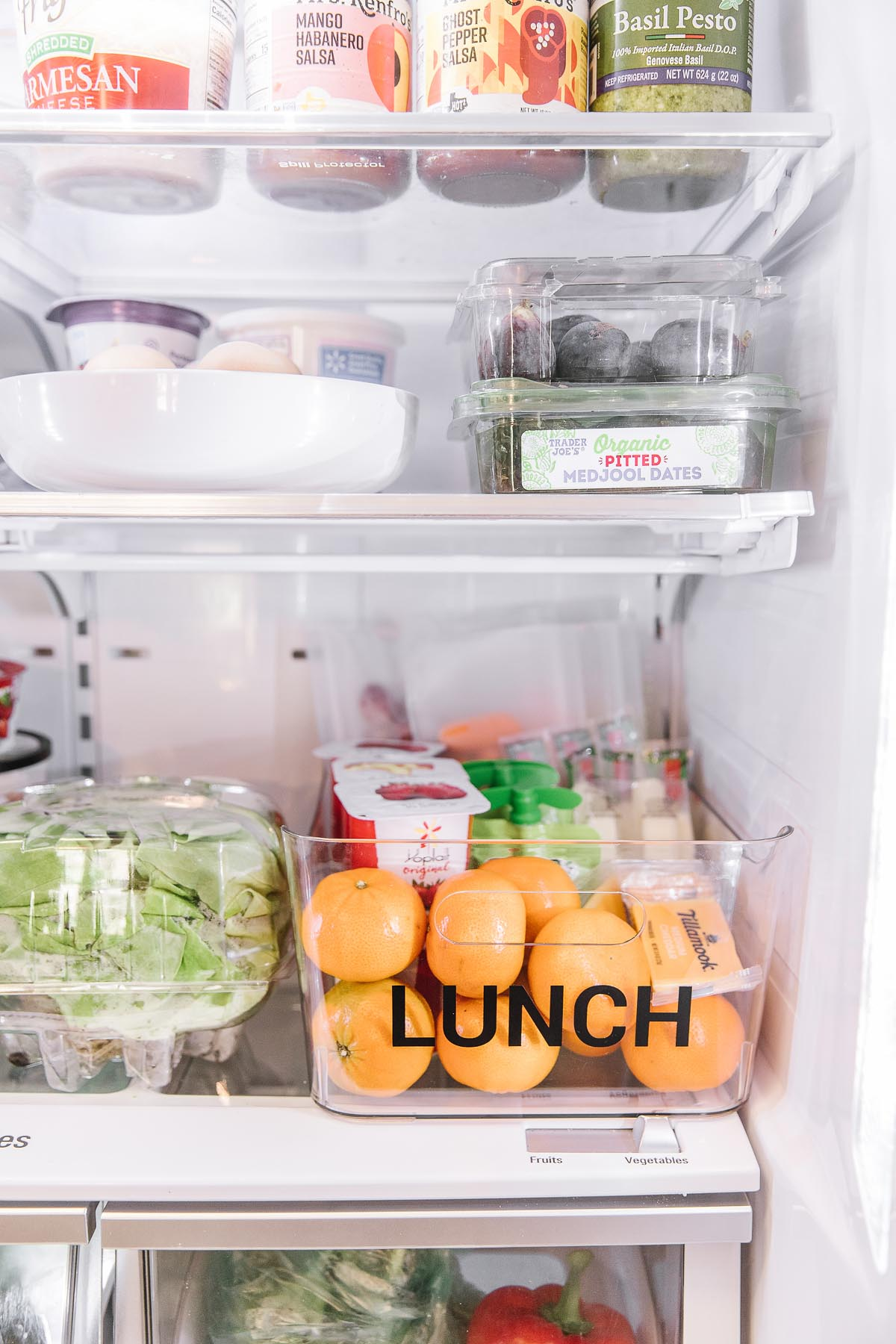 A fridge filled with food including a plastic container with the word lunch in black letters filled with oranges, yogurt, applesauce, cheese and veggies. Perfect school lunch ideas!