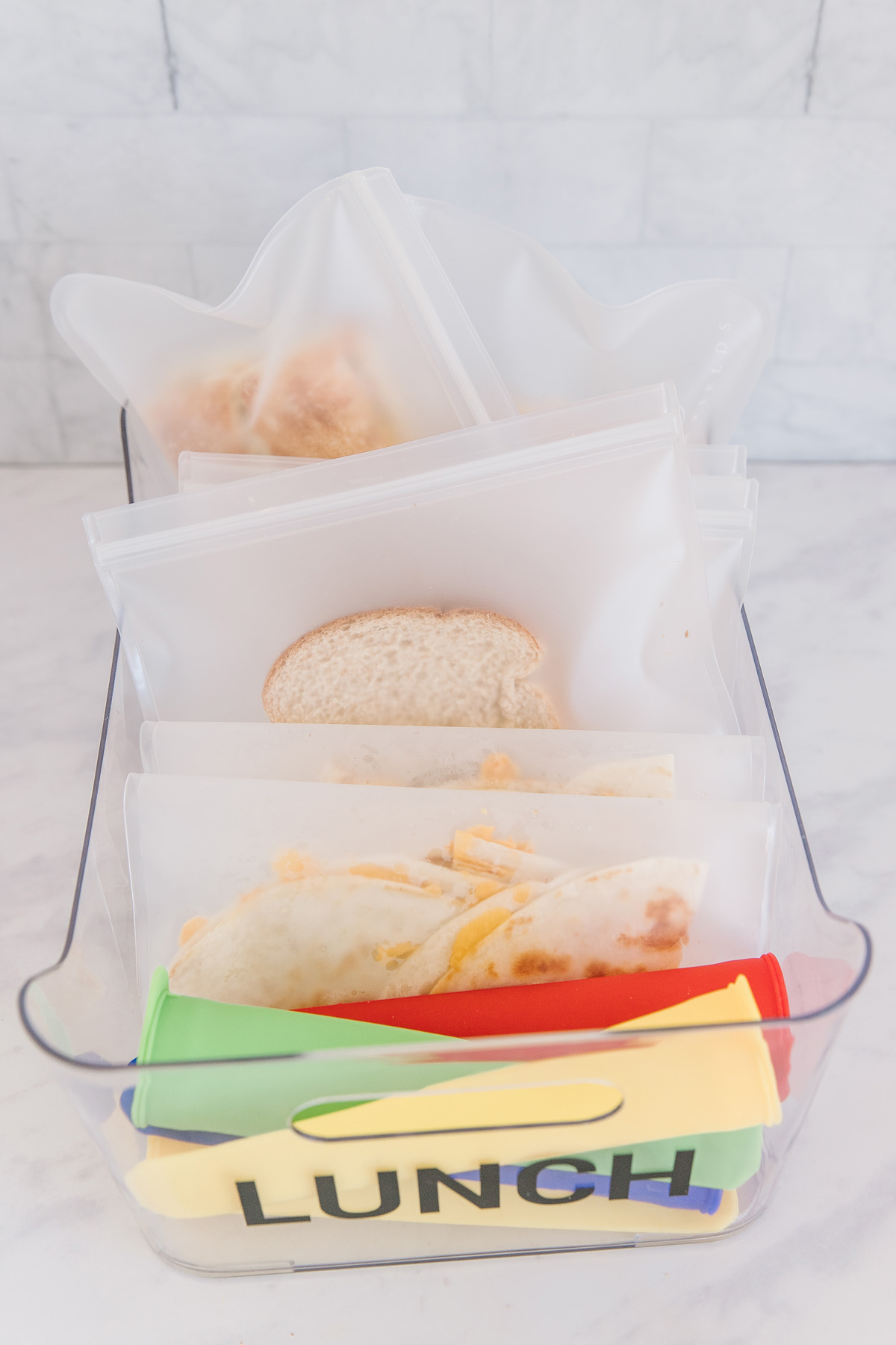 A plastic container with yogurt pops and resealable bags with cheese quesadillas and sandwiches.