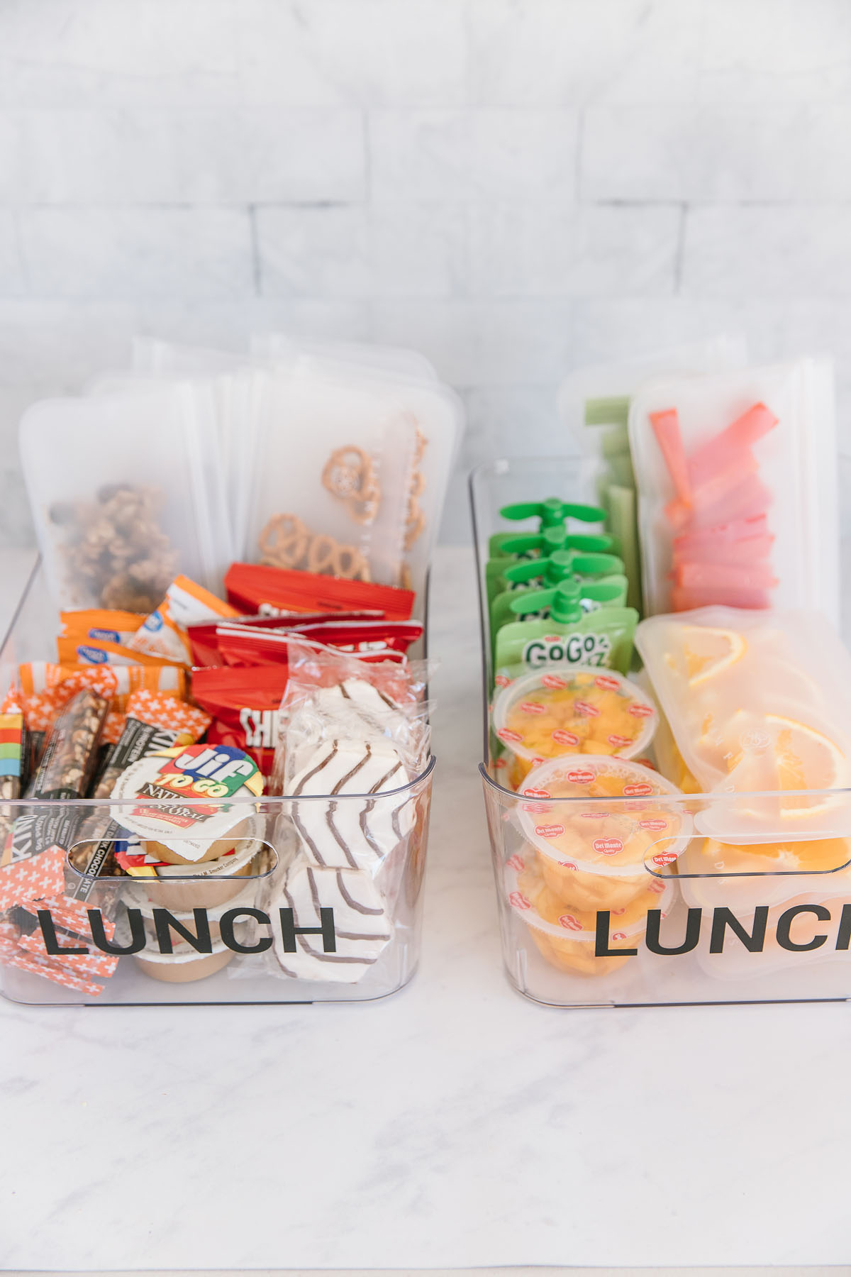 Two plastic containers with the word lunch on both of them. One is filled with prepackaged fruit and veggies and one is filled with packaged snacks, nuts, peanut butter, crackers and pretzels.