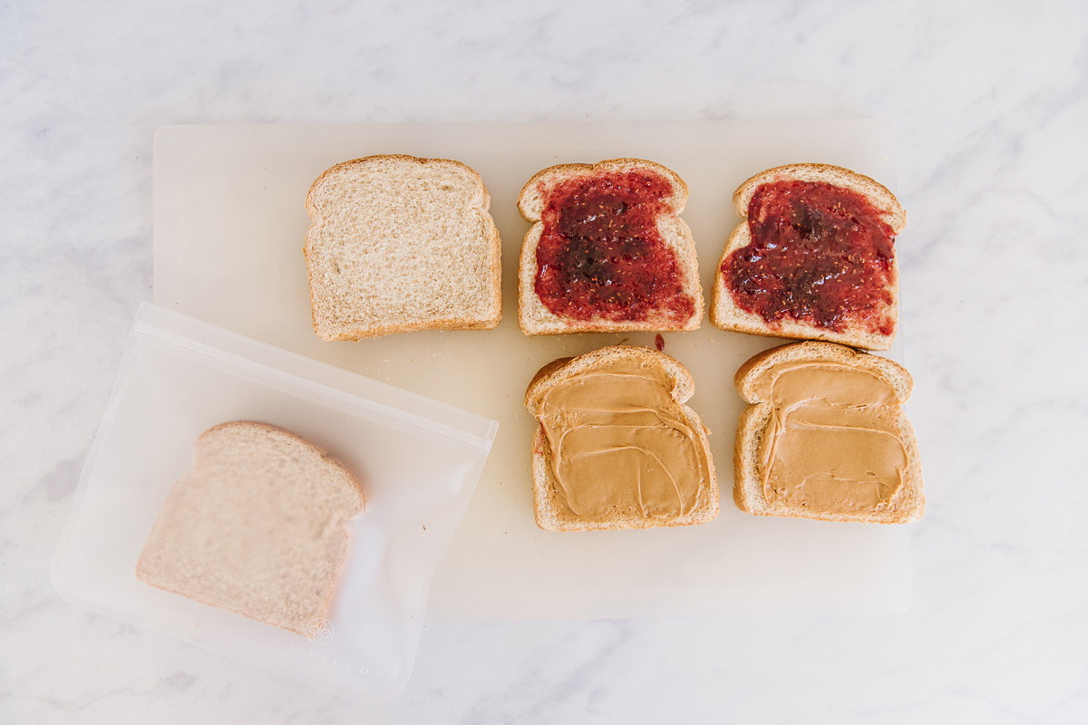 Six slices of bread laid out - two slices have jelly on them, two have peanut butter on them. One is plain and one is plain in a resealable bag.
