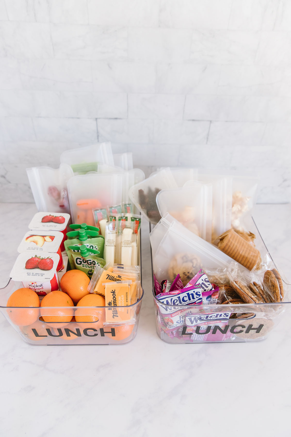 Two plastic containers with the word lunch on both of them. One is filled with prepackaged fruit, cheese and veggies and one is filled with packaged snacks, nuts, peanut butter, crackers and pretzels.