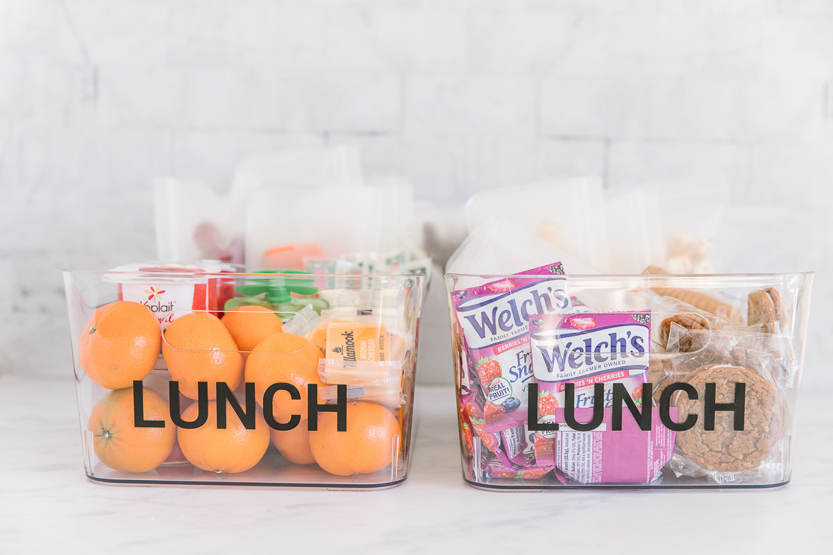 Two plastic containers with the word lunch on both of them filled with snacks like oranges, yogurt, applesauce and fruit snacks and packaged cookies. Perfect school lunch ideas!