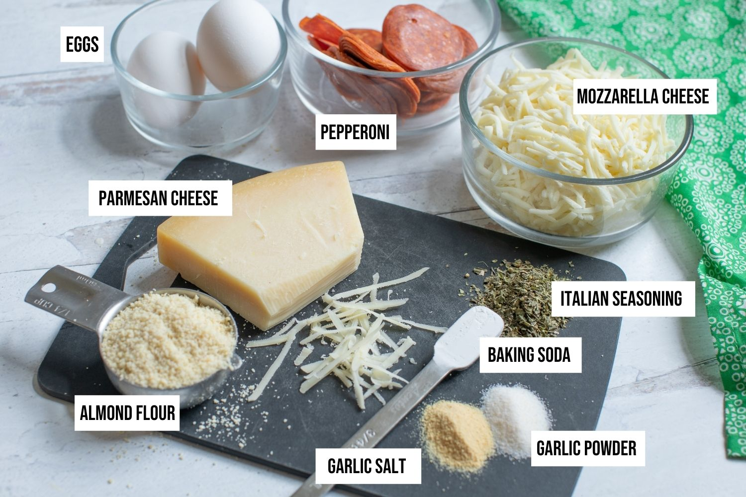 Ingredients in glass bowls are whole eggs, pepperoni slices, shredded mozzarella cheese.  Ingredients on a cutting board are seasonings, flour and cheese.