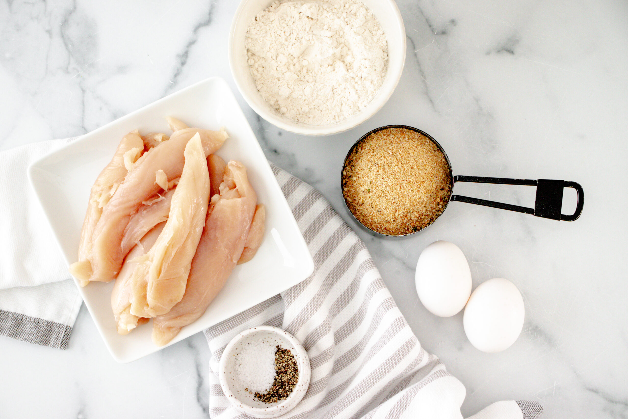 A white plate with raw chicken and a white bowl of flour, eggs, panko and seasonings.