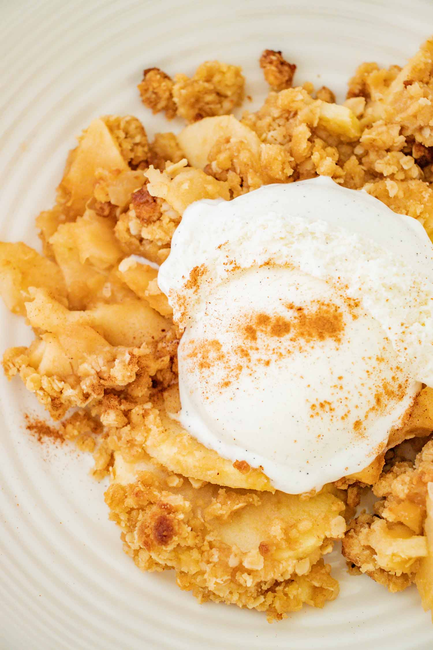 Closeup shot of apple crisp with vanilla ice cream on a white plate