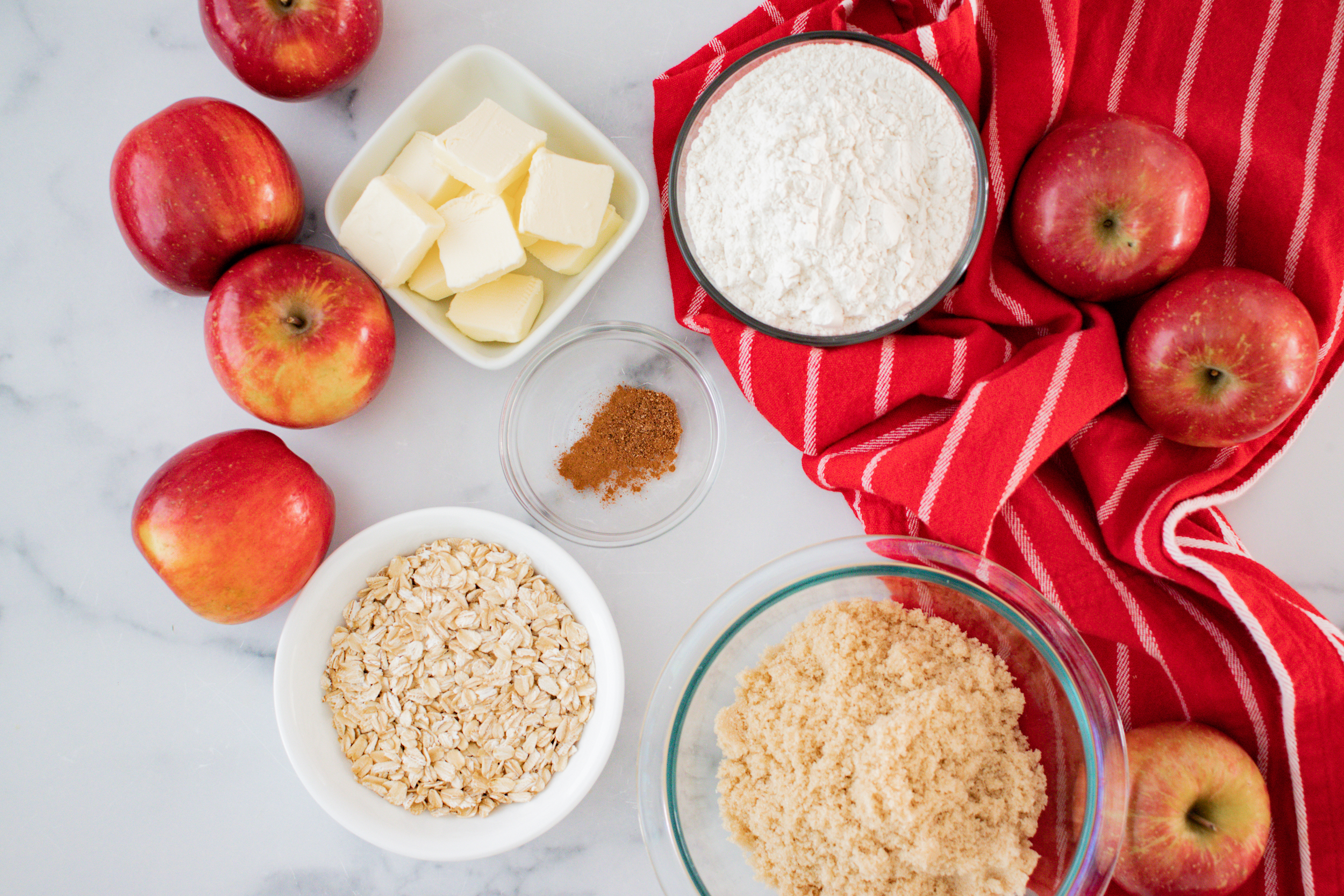 ingredients for apple crisp including butter in a white bowl, flour, cinnamon, oats and brown sugar in individual bowls and a red napkin.