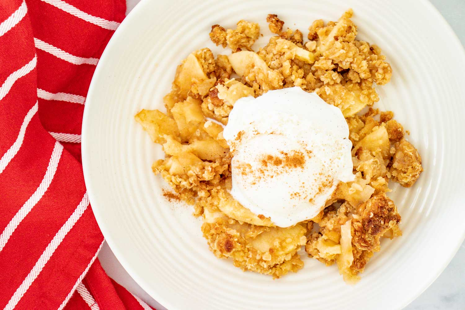 white plate with apple crisp and a scoop of vanilla icecream sprinkled with cinnamon and a red napkin