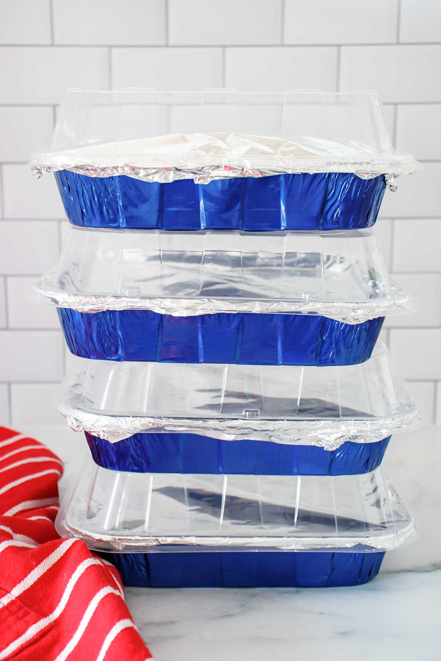 4 stacked blue aluminum foil baking pans filled with freezable apple crisp.