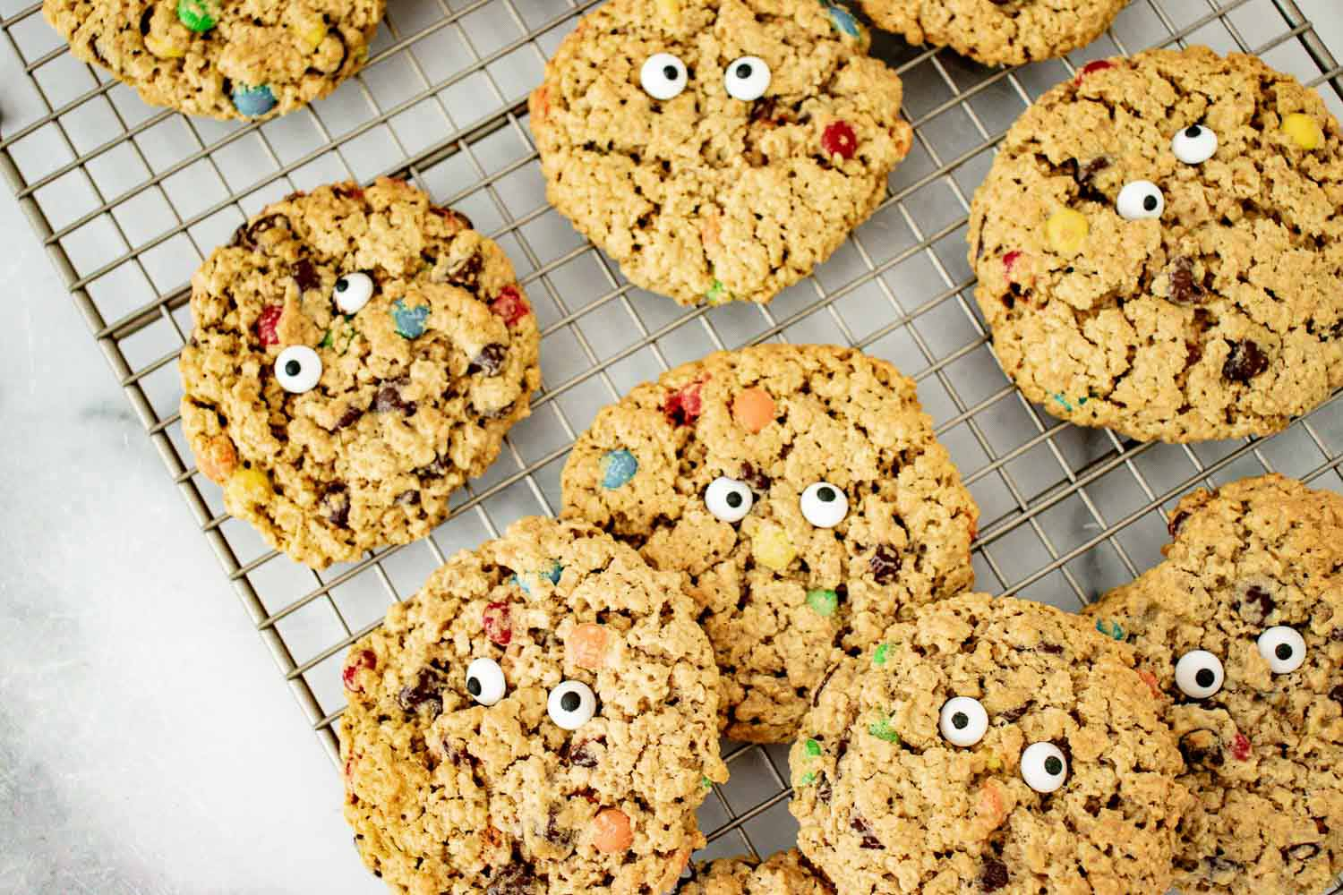 Baked monster cookies with eyes on them sitting on a wire rack.