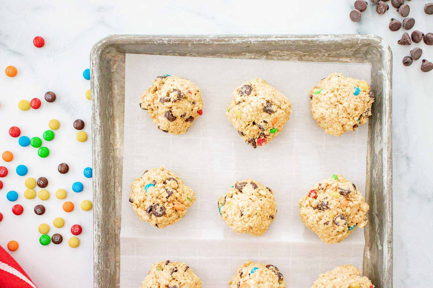 A cookie sheet with a parchment paper with unbaked cookie balls on it and a silver bowl with more cookie dough to the side of it.