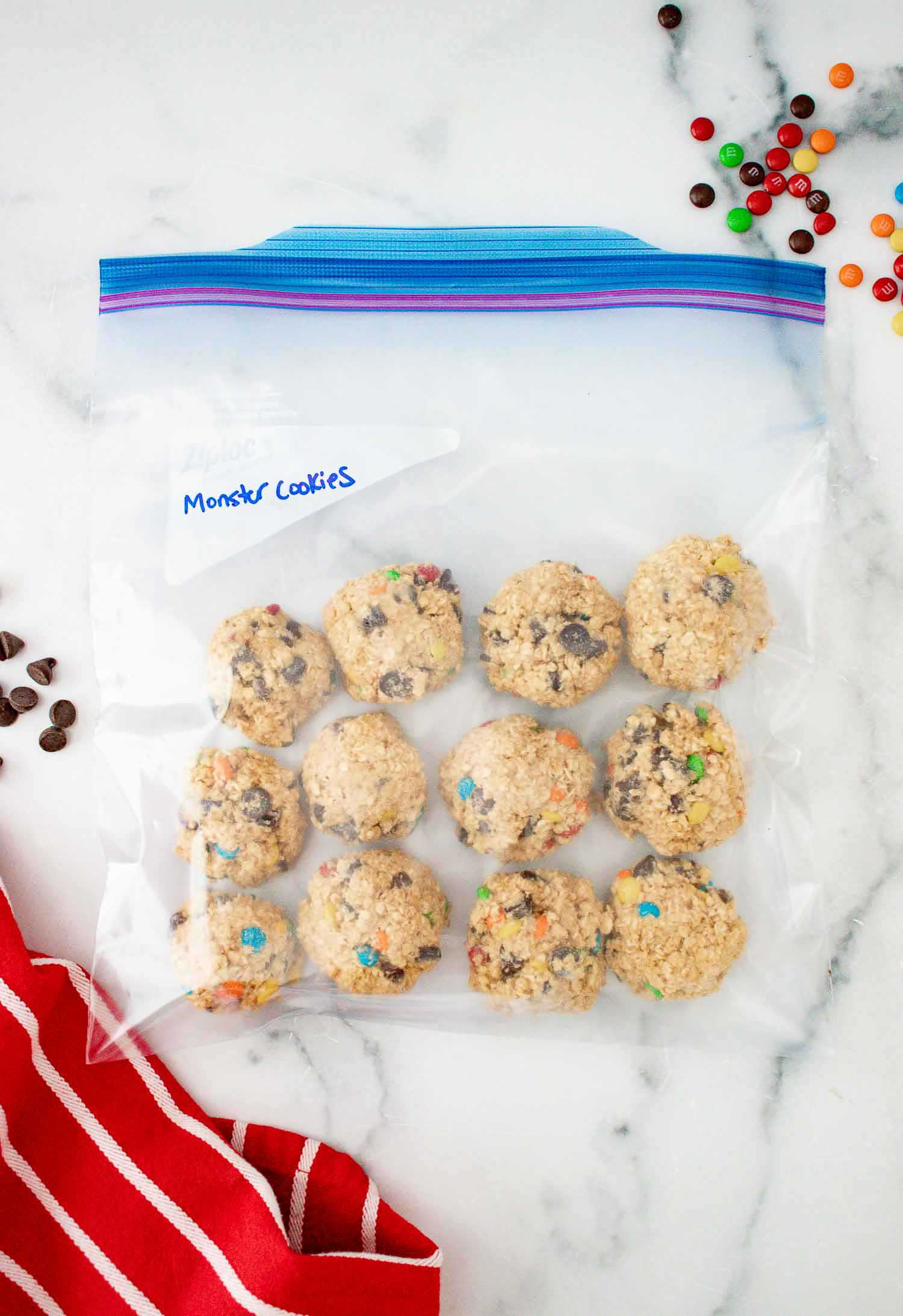 """A freezer ziploc bag with unbaked monster cookies in it with the words """"monster cookies"""" written on it."""