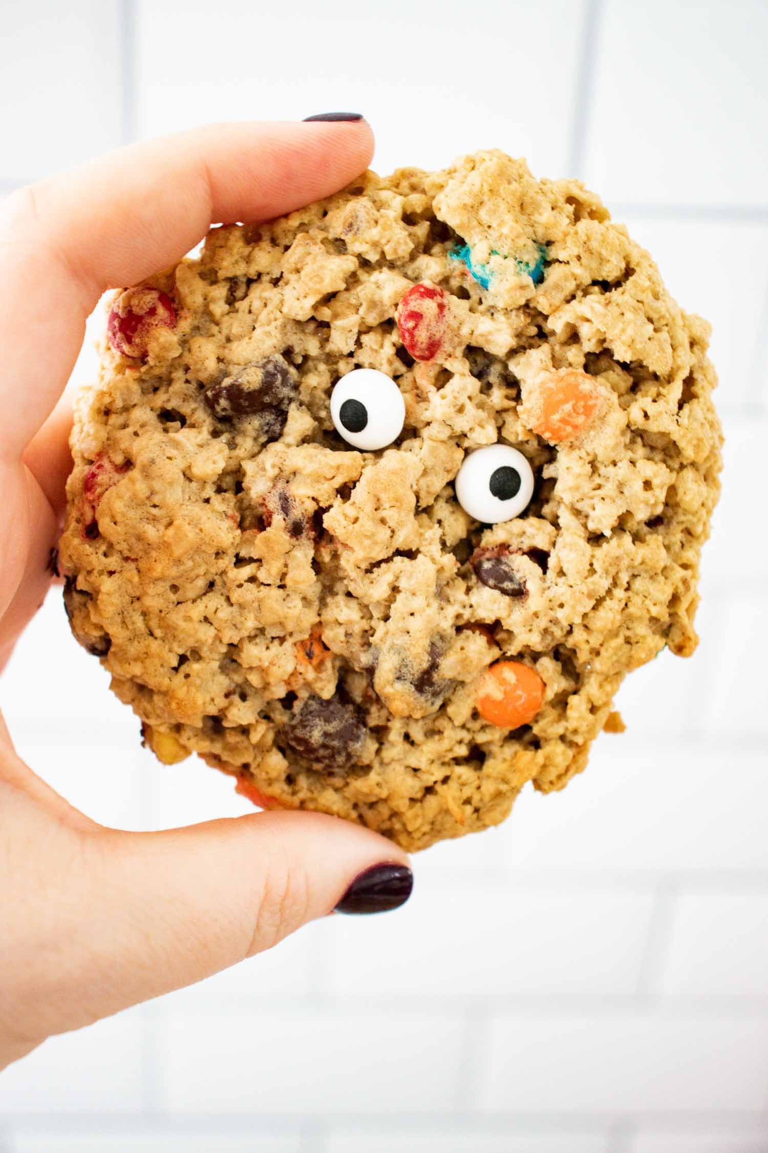 A hand holding a single monster cookie with eyes on it.