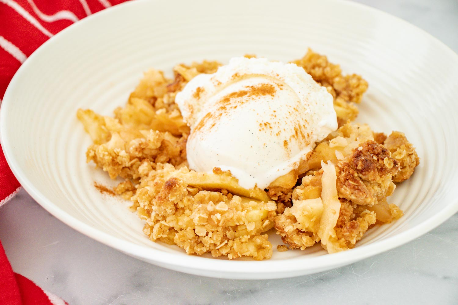 white bowl filled with apple crisp and a scoop of vanilla ice cream sprinkled with cinnamon