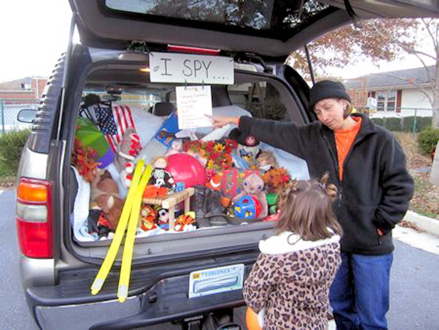 An open SUV truck with stuffed animals in it with a sign saying I Spy with two people looking at it.