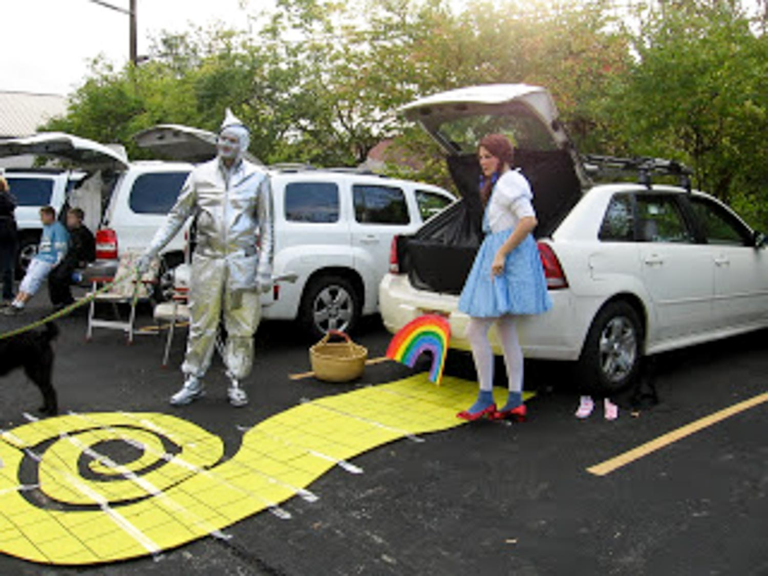 A yellow brick road leading to a open car trunk with a basket and rainbow and characters next to it.
