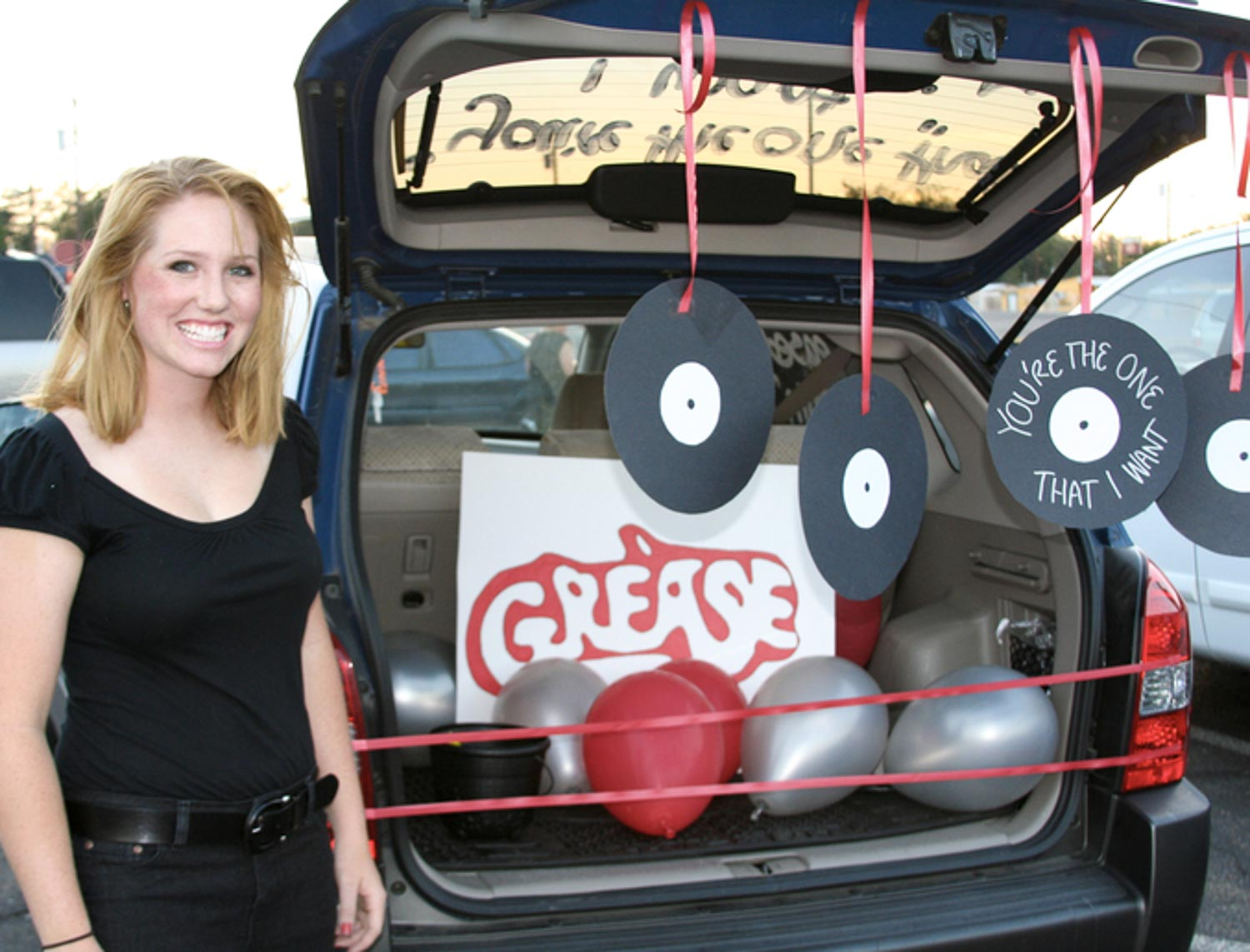An open car trunk with records hanging down with a Grease sign and balloons in it with a girl in black next to it.