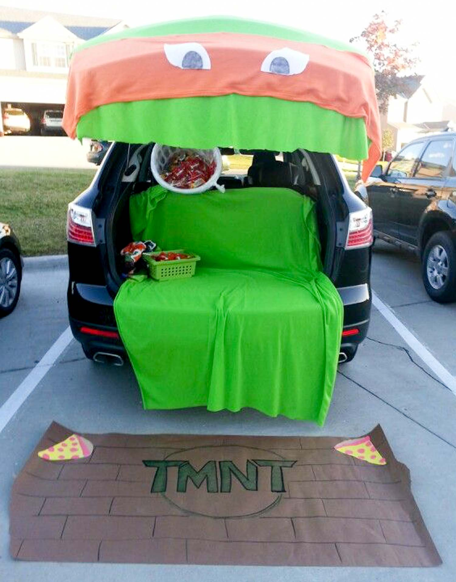 A teenage mutant ninja turtle cover over an open SUV trunk with a green blanket in it and a brown carpet with TMNT and pizzas on it.