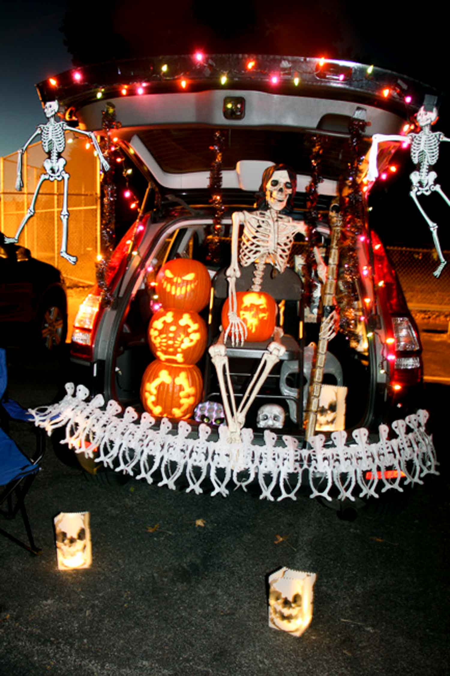 A trunk decorated with skeletons, pumpkins and lights for a spooky Halloween night.