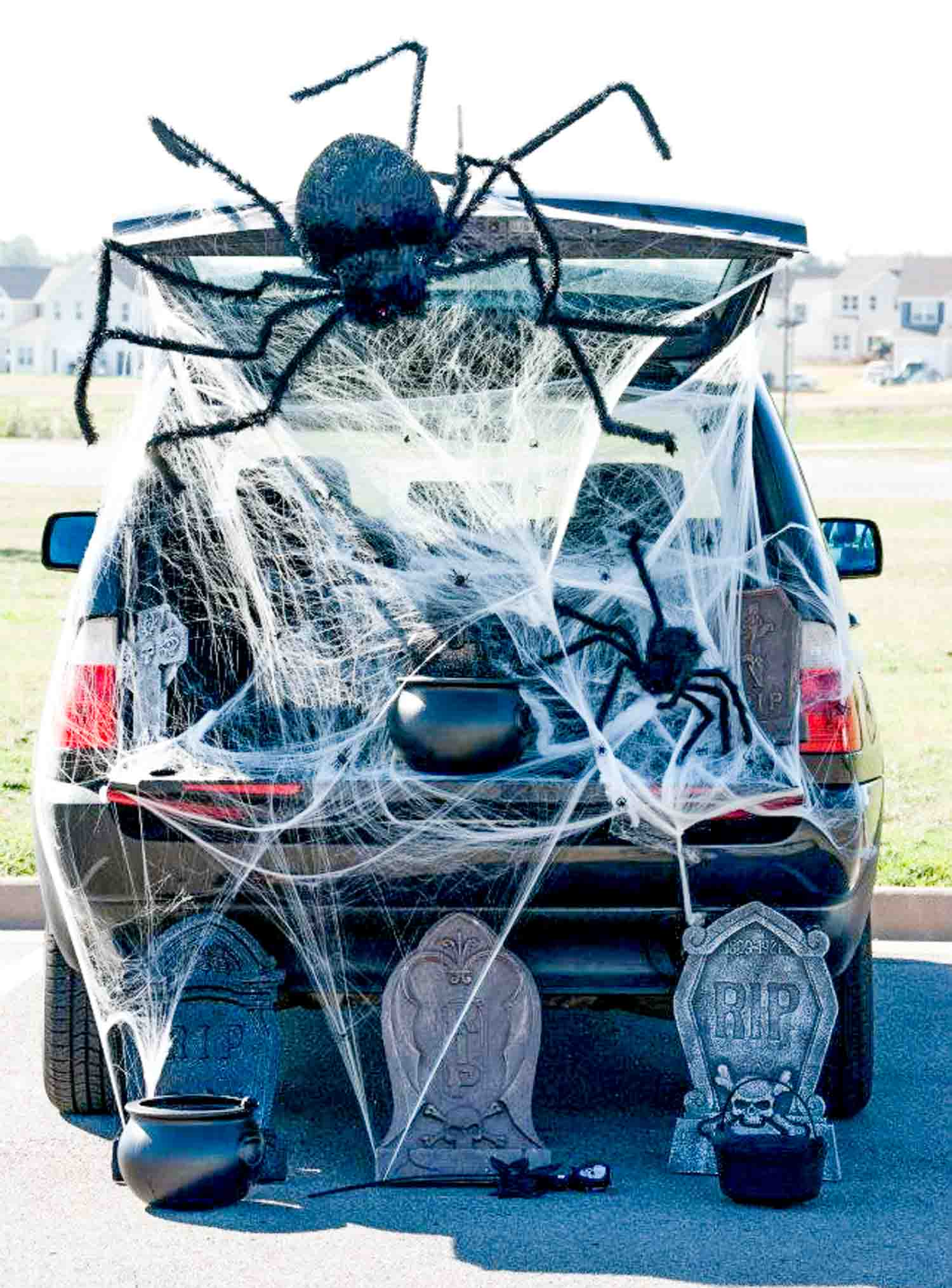 Two huge spiders in a spider web in an open trunk with a black cauldron and three gravestones on the ground - easy trunk or treat idea for SUV's!