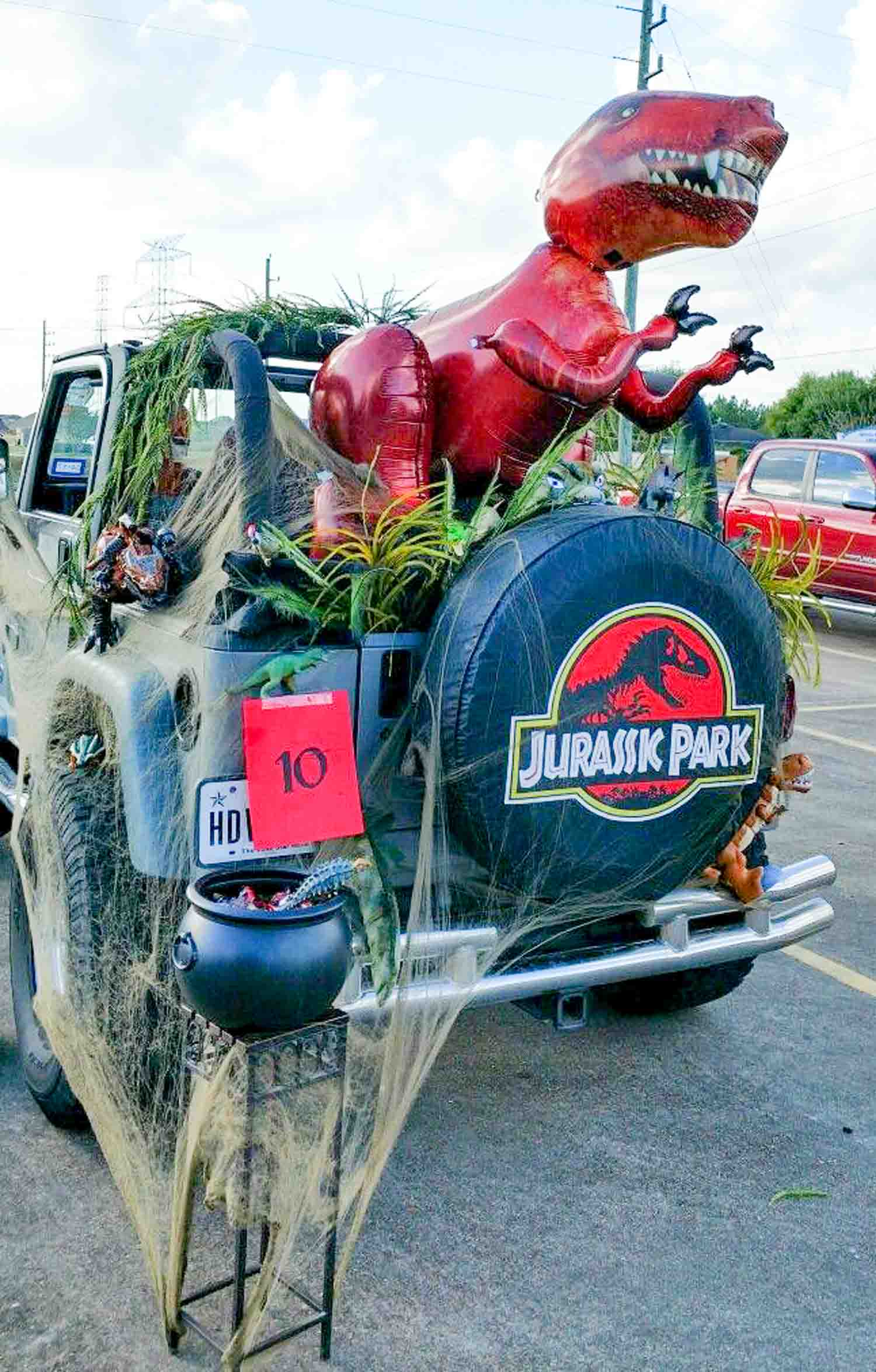 A jeep filled with plants and an inflatable dinosaur with a black covering saying Jurassic Park.