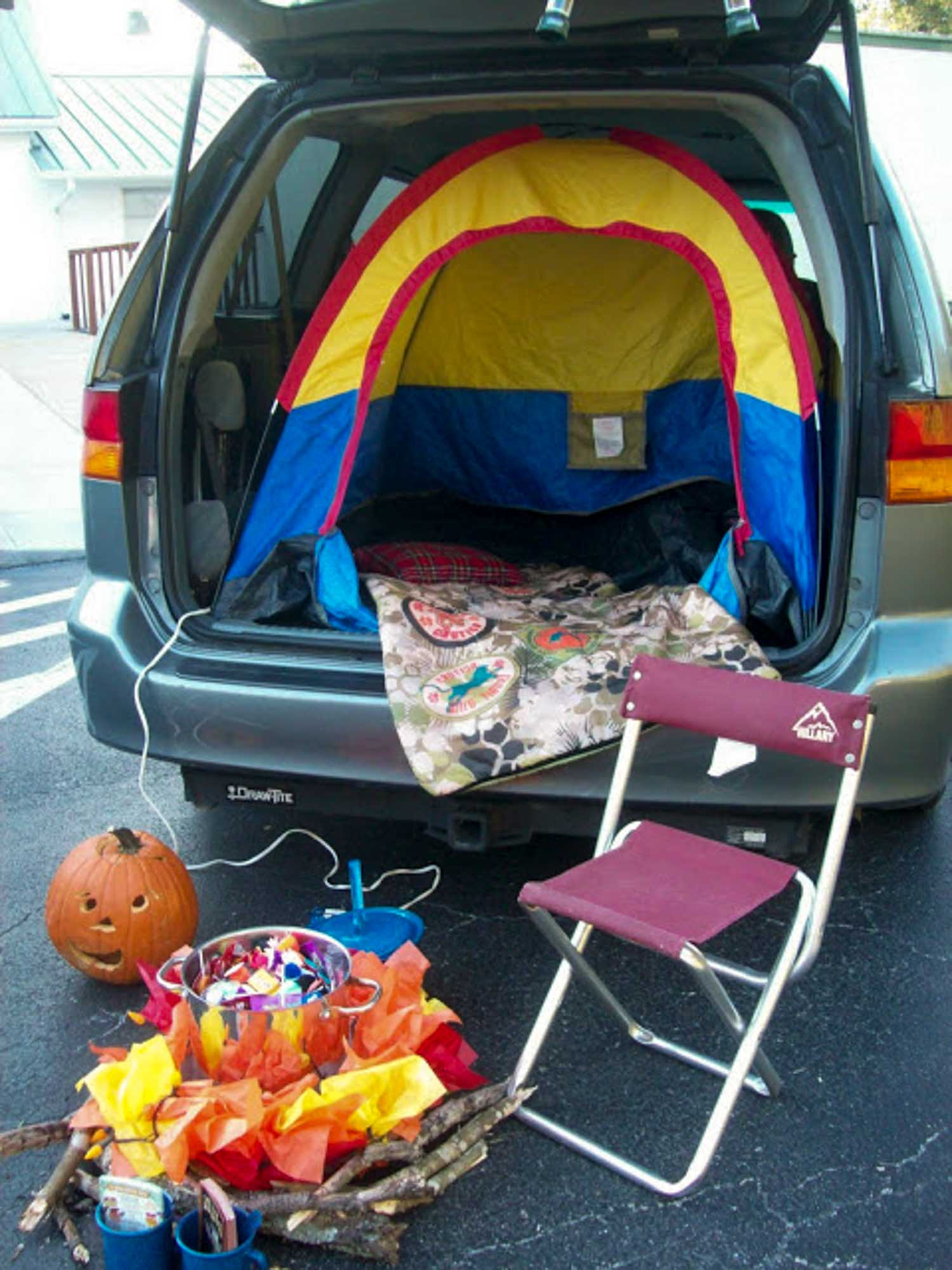 A tent in the back of an open SUV with a chair and a fake fire outside of it - perfect ideas for pickup trucks!