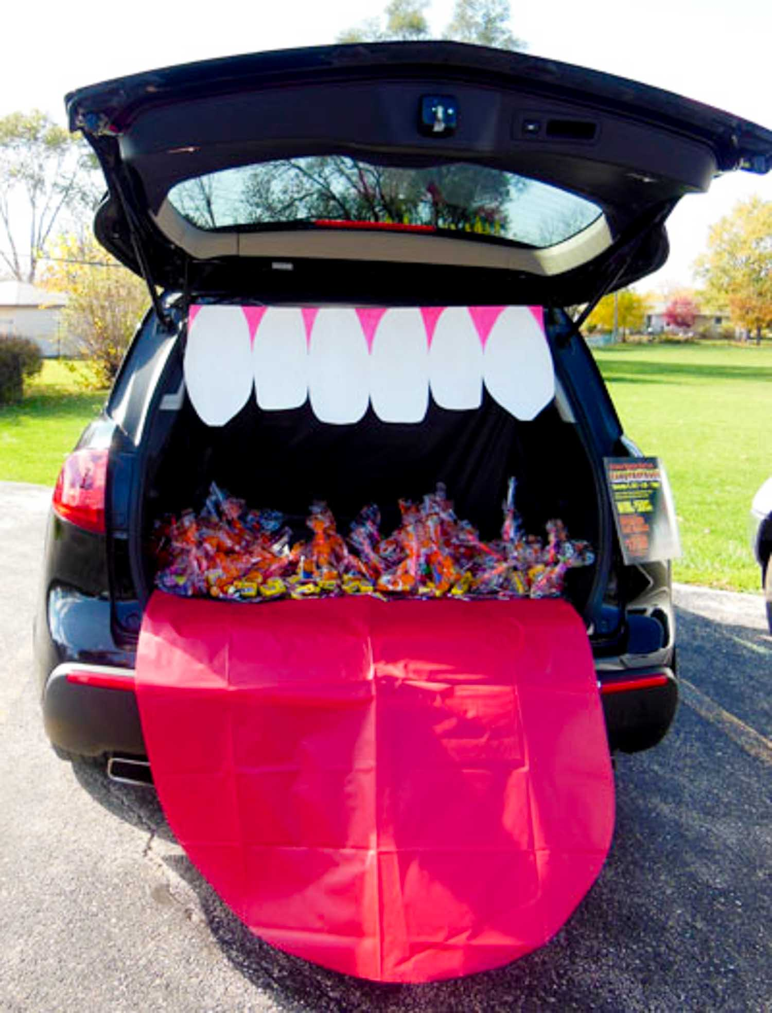 A large mouth decor in the back of a trunk with candy bags inside of it.