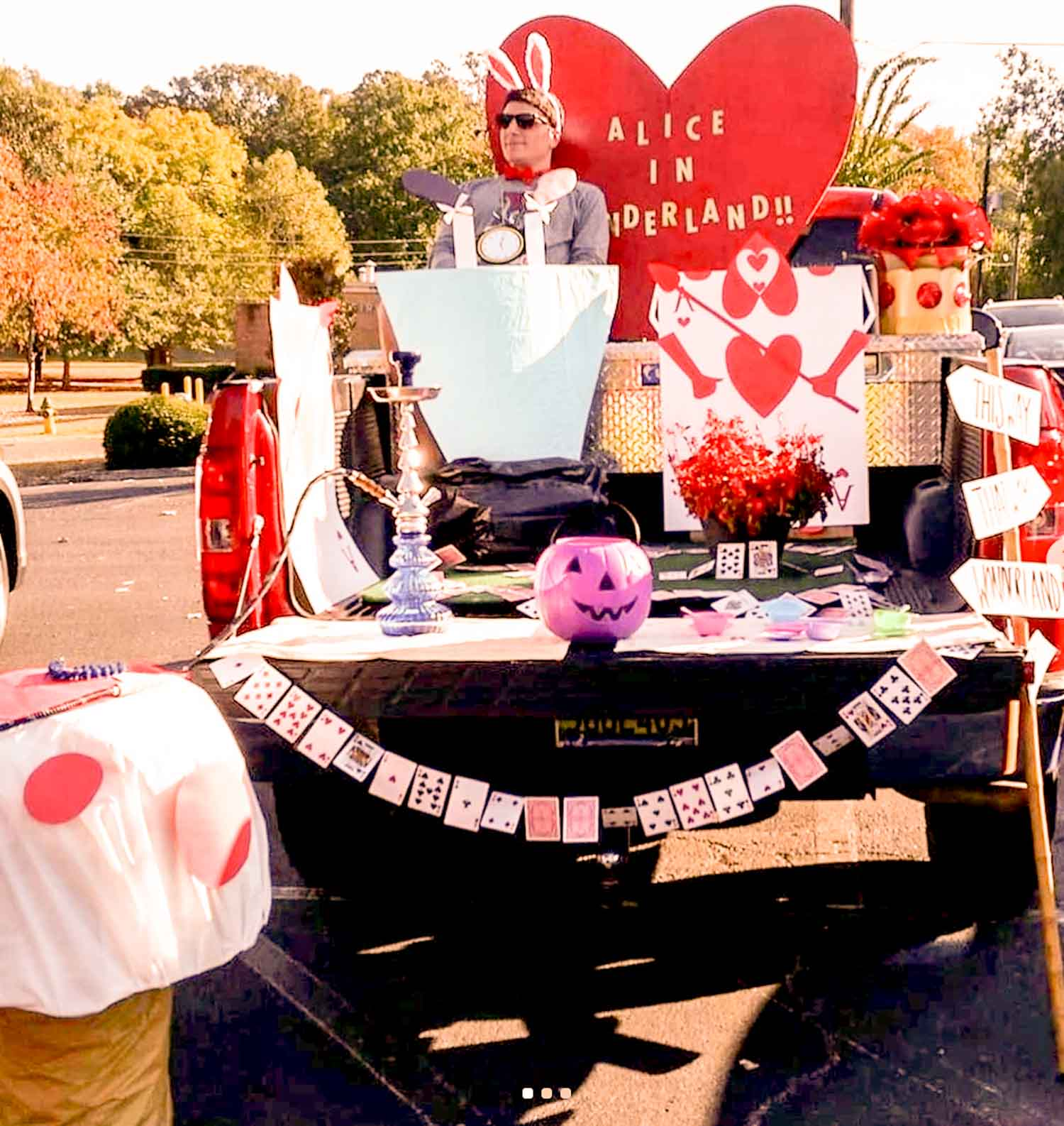 An Alice in Wonderland themed truck bed idea with a person dressed as the white rabbit in it.